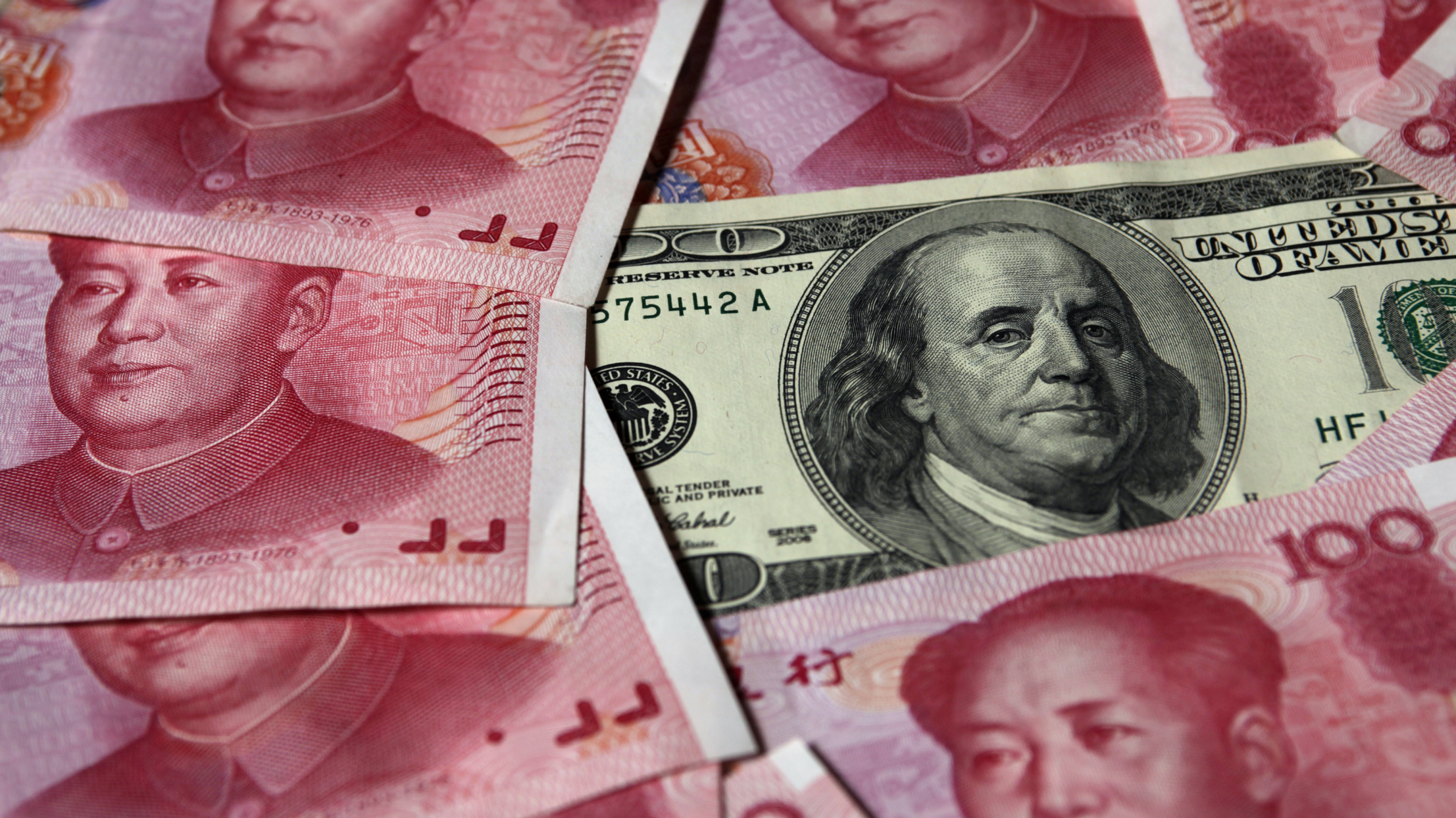 A U.S. $100 banknote is placed next to 100 yuan banknotes in this picture illustration taken in Beijing October 16, 2010. The United States fired the first shot in the currency war and the rest of the world must be on guard for its deliberate strategy to devalue the dollar, a Chinese economist said in an official newspaper on Thursday. REUTERS/Petar Kujundzic