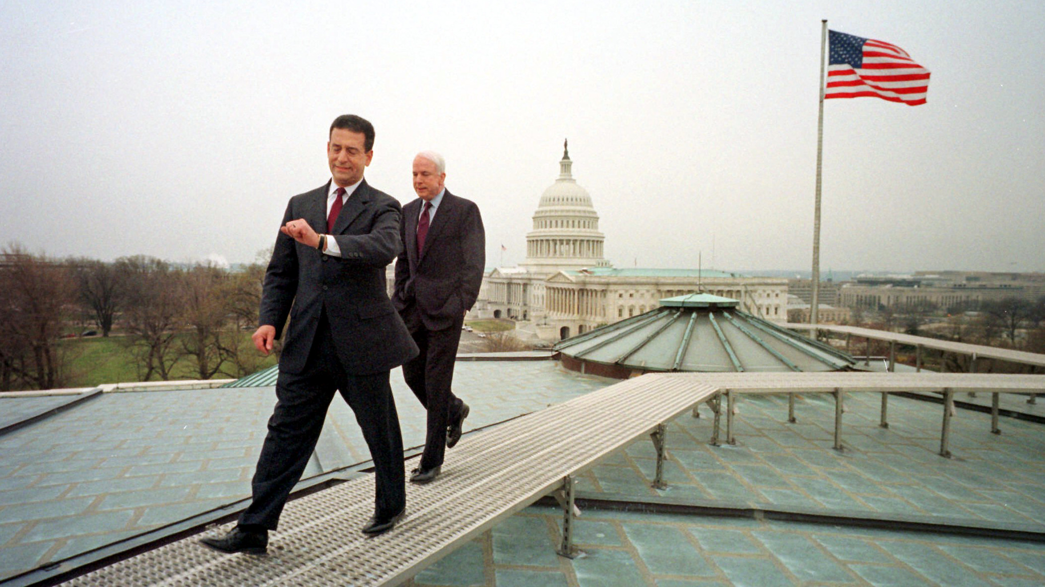 In this March 29, 2001 photo, U.S. Sen. Russ Feingold, D-Wis, checks his watch as he and Sen. John McCain, R-Ariz., walk off the roof of the Russell office building on Capitol Hill after an early morning Time Magazine photo session Thursday morning March 29, 2001 in Washington.