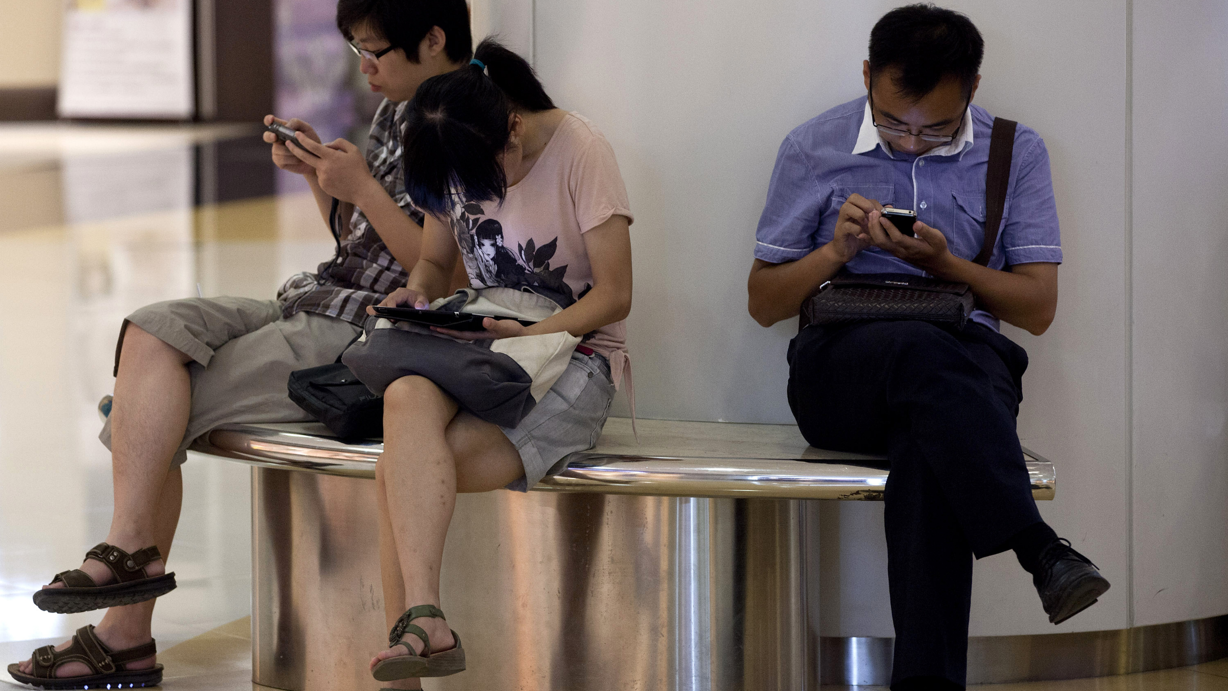 People sit on a bench inside a shopping mall using their tablet computer and smartphone in Beijing, China Monday, Aug. 19, 2013. Many famous Chinese - from pop stars to scholars, journalists to business tycoons - have amassed substantial online followings, and these larger-than-life personalities don't always hew to the Communist Party line. Now Beijing is tightening its grip on China's already heavily restricted Internet by making influential microbloggers uncomfortable when they post material the government doesn't like. (AP Photo/Andy Wong