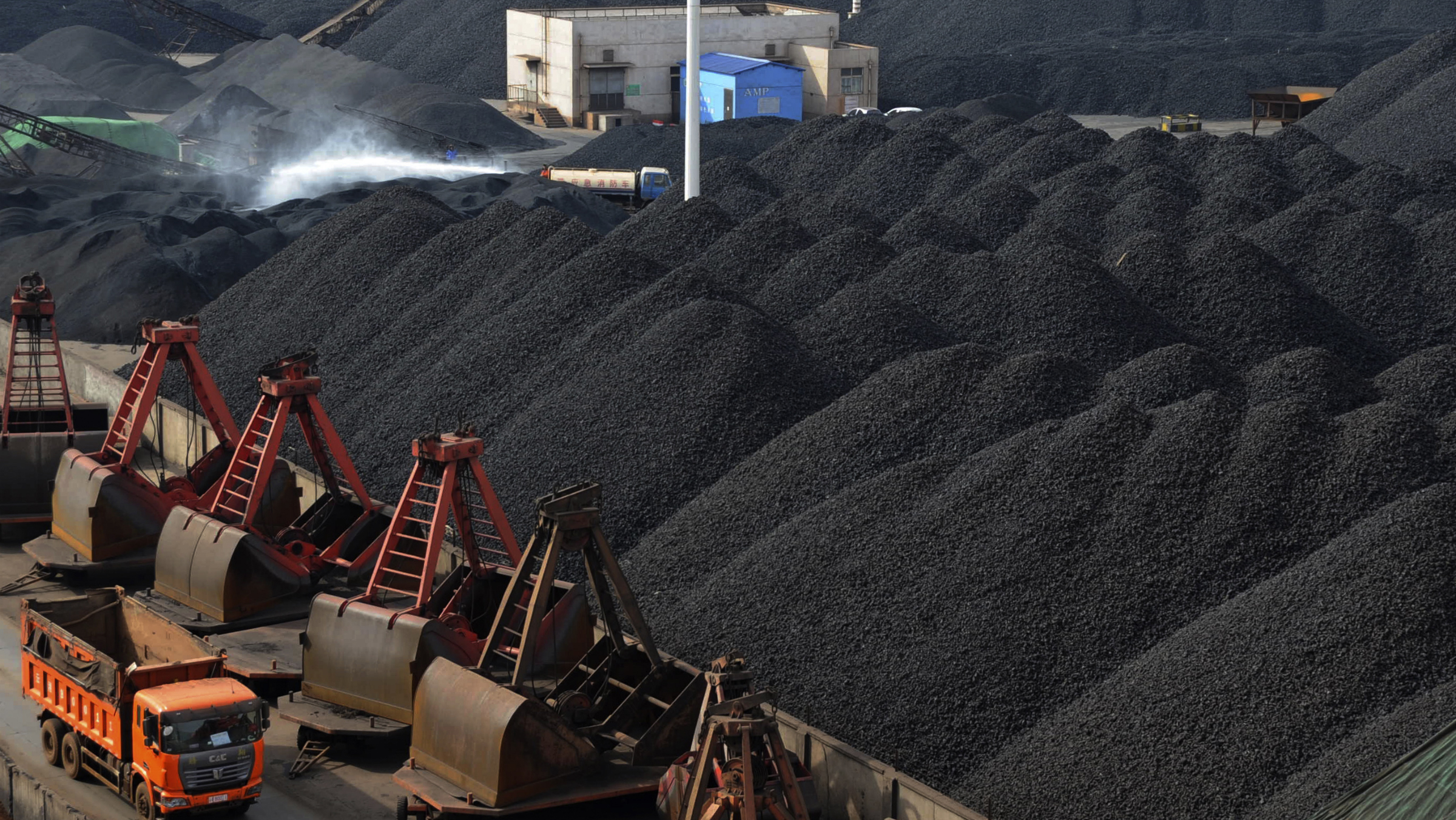 A truck drives past as a worker sprays water at a coal pier of Lianyungang port, Jiangsu province February 26, 2012. China's power consumption is likely to grow 8.8 percent annually between 2011 and 2015 to 6.02-6.61 trillion kilowatt hours, the China Securities Journal said on Monday, citing the China Electricity Council, an association of power producers. Picture taken February 26, 2012. REUTERS/China Daily