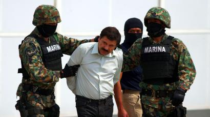 """Joaquin """"El Chapo"""" Guzman is escorted to a helicopter in handcuffs by Mexican navy marines at a navy hanger in Mexico City, Mexico, Saturday, Feb. 22, 2014. A senior U.S. law enforcement official said Saturday, that Guzman, the head of Mexico's Sinaloa Cartel, was captured alive overnight in the beach resort town of Mazatlan. Guzman faces multiple federal drug trafficking indictments in the U.S. and is on the Drug Enforcement Administration's most-wanted list."""
