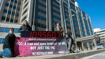 Members of global advocacy group Avaaz stand next to a digital counter showing the number of petition signatures calling for net neutrality outside the Federal Communication Commission in Washington, Thursday, Jan. 30, 2014. Avaaz joined other US advocacy groups to deliver more than a million signatures for a free and democratic internet to the FCC.