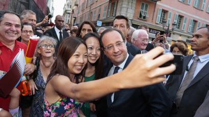 Chinese tourists take a photo of themselves with France's President Francois Hollande ahead of the opening ceremony of the 7th Francophone Games in Nice September 7, 2013. REUTERS/Eric Gaillard