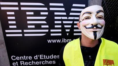 An IBM labour union employee wears an anonymous mask as he demonstrates in La Gaude, August 9, 2012, against the relocation of 70 jobs to Poland and the Czech Republic.