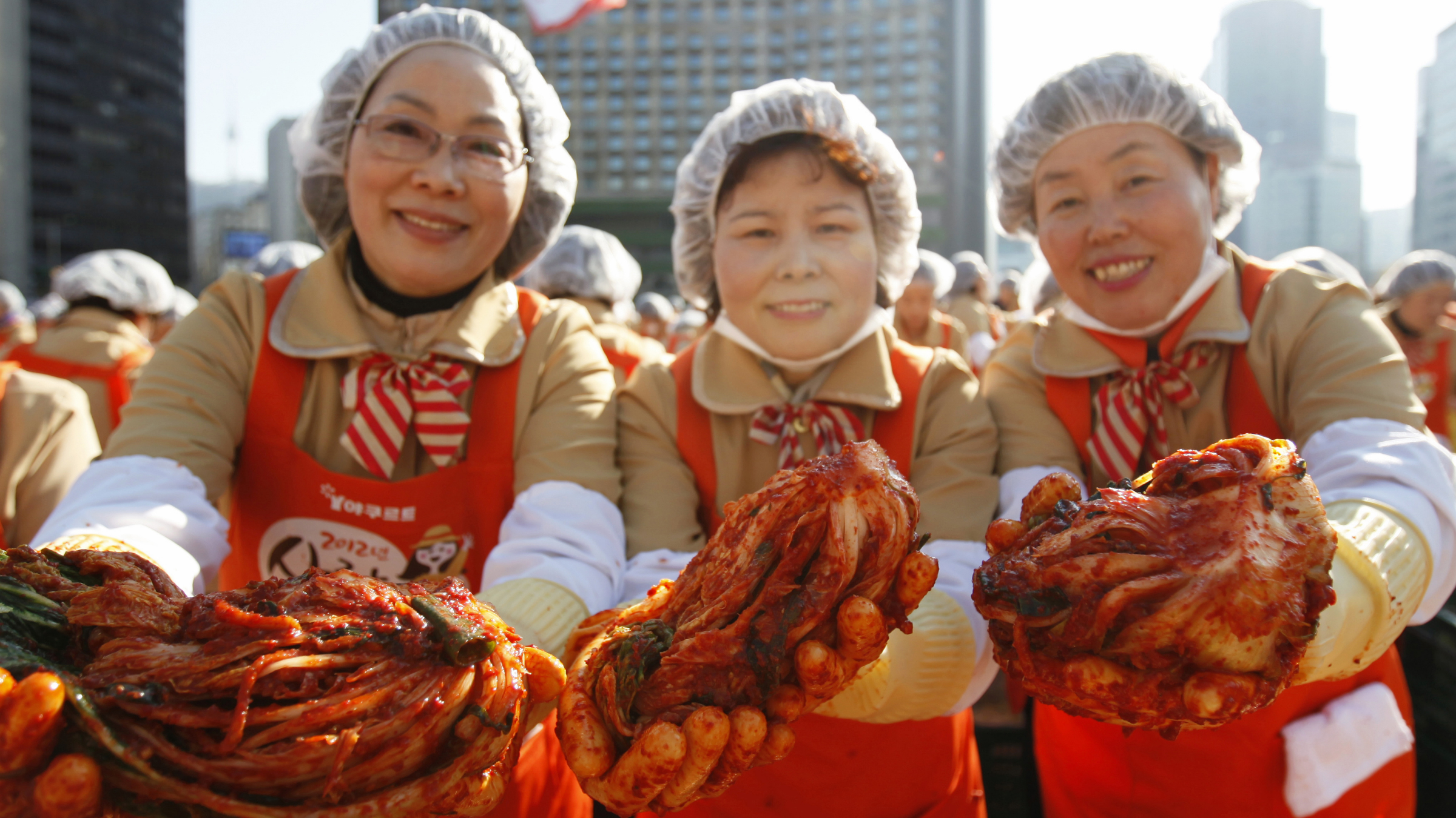 Women pose for photos holding kimchi as they make the traditional Korean side dish consisting of fermented cabbage, at a charity event at Seoul City Hall Plaza November 15, 2012. More than 2,000 volunteers made 270 tonnes of kimchi on Thursday to give away to needy people during the winter season. REUTERS/Kim Hong-Ji