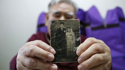 A South Korean man holds up a photo of his younger brother, a North Korean.