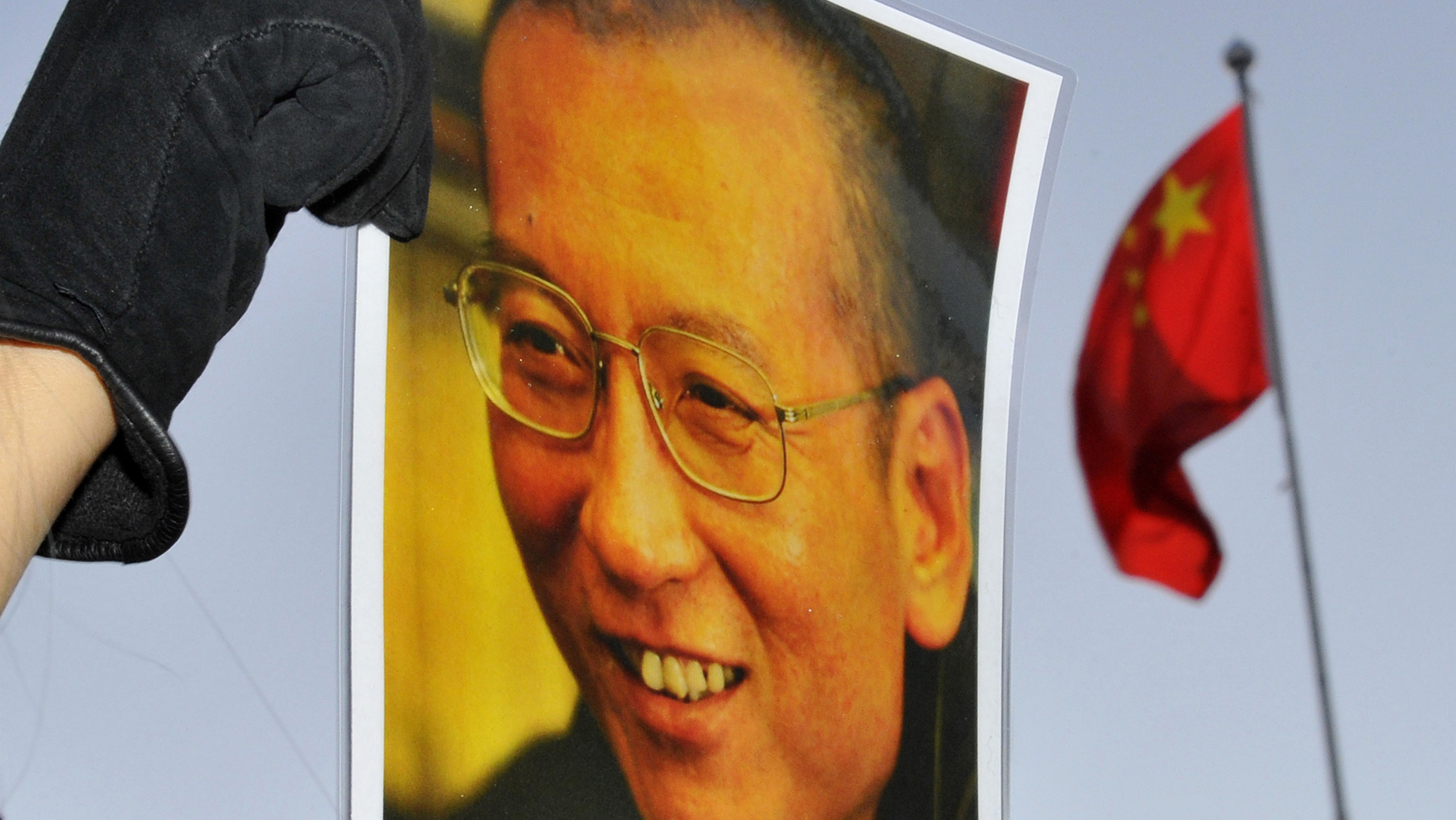 """A protester holds an image of to jailed dissident Liu Xiaobo outside of the Chinese Embassy in Oslo December 9, 2010. The Nobel Peace Prize panel on Thursday defended its award to jailed dissident Liu as based on """"universal values"""", rejecting Beijing's accusation that it is trying force Western ideas on China. The Nobel Peace Prize will be awarded to Liu Xiaobo on Friday. REUTERS/Toby Melville"""