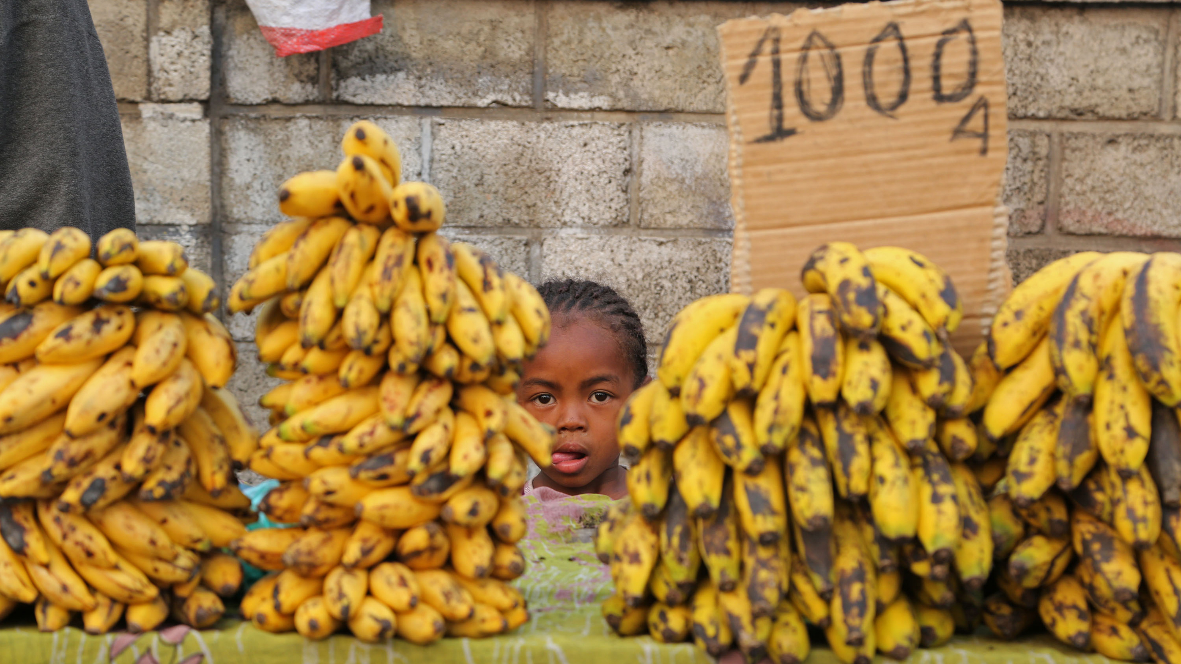A girl stands behind her father's banana store in the city of Antananarivo, Madagascar, Wednesday, Oct. 23, 2013. Madagascar will hold elections on Friday that organizers hope will end political tensions that erupted in a 2009 coup and help lift the aid-dependent country out of poverty. The island nation in the Indian Ocean plunged into turmoil after Andry Rajoelina, the current president, forcibly took power from former President Marc Ravalomanana with the backing of the military. (AP Photo/Schalk van Zuydam