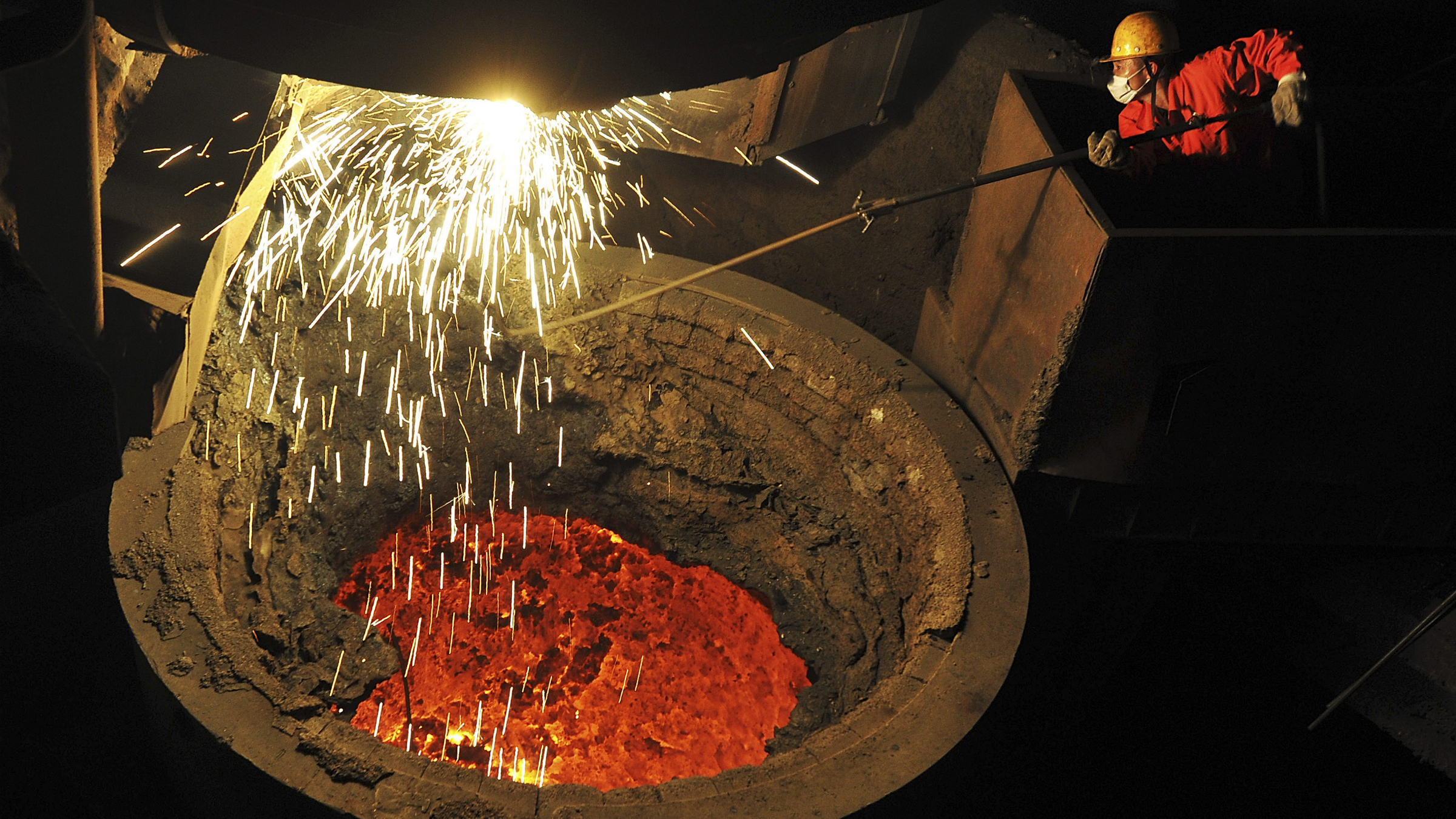 An employee works above a furnace containing molten steel at a factory of Dongbei Special Steel Group Co. Ltd. in Dalian, Liaoning province January 30, 2014. China's factory growth eased to an expected six-month low in January, hurt by weaker local and foreign demand, a survey showed, a soft start for the year that heightens worries of an economic slowdown. The official Purchasing Managers' Index (PMI) edged down to 50.5 in January from December's 51, the National Bureau of Statistics said on Saturday, in line with market expectations. Picture taken January 30, 2014. REUTERS/China Daily