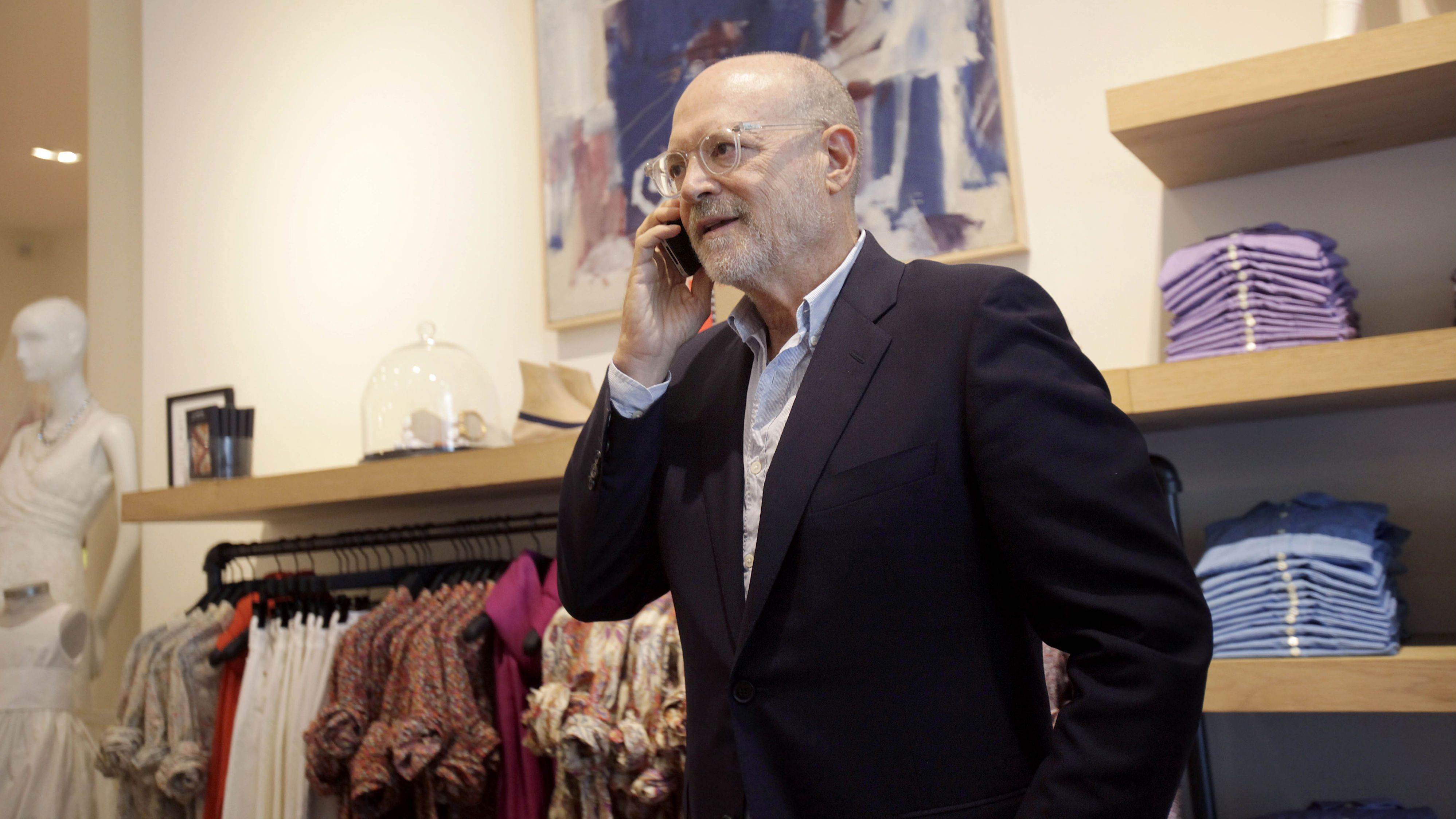 "This Aug. 8, 2012 photo shows J. Crew CEO Millard ""Mickey"" Drexler speaking on the phone at a J. Crew store in New York. Under his leadership, J. Crew has carved out a place in the fashion hierarchy that's just between trendsetter and accessible, and Drexler seems to like living in that space. (AP Photo/Seth Wenig)"