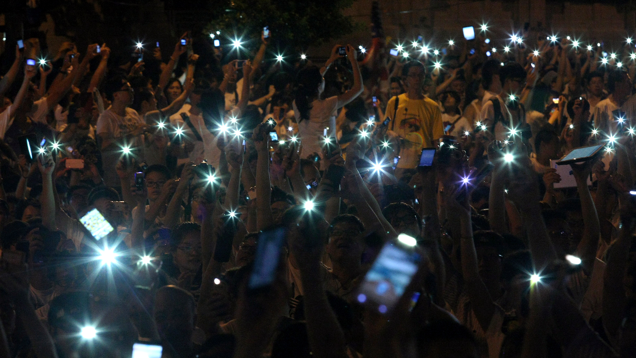 People wave cell phones as they take part in a demonstration in front of the Presidential Office in Taipei August 3, 2013. Hundreds of thousands of demonstrators gathered on Saturday to mourn for soldier Hung Chung-chiu, who died of organ failure after suffering a heatstroke caused from performing punishment exercises on July 4, and to demand further investigation into Hung's case, according to event organizers.