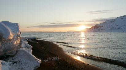 The sun shines low in the sky just after midnight over a frozen coastline near the Norwegian Arctic town of Longyearbyen, April 26, 2007. The sea water is normally frozen solid at this time of year but global warming may be warming the region. REUTERS/Francois Lenoir