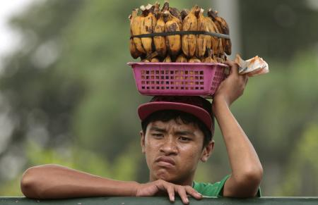 A Filipino boy selling boiled bananas rests on a steel fence in Quezon city, north of Manila, Philippines on Wednesday, Sept. 11, 2013. (AP Photo/Aaron Favila