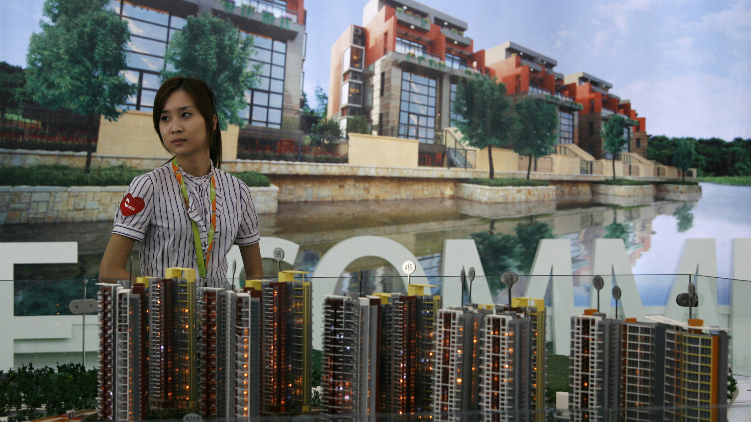 A sales agent waits for customer in front of the model of a property development at the 5th China (Shenzhen) Real Estate Fair, in the southern Chinese city of Shenzhen May 4, 2010. Chinese property prices are looking bubbly and the government is stepping up its efforts to take the market off the boil. In contrast to regional neighbours, China has so far eschewed the blunter instrument of higher borrowing costs, not least because it harbours doubts about the solidity of the global recovery and has an eye on the all-important property market. REUTERS/Bobby Yip