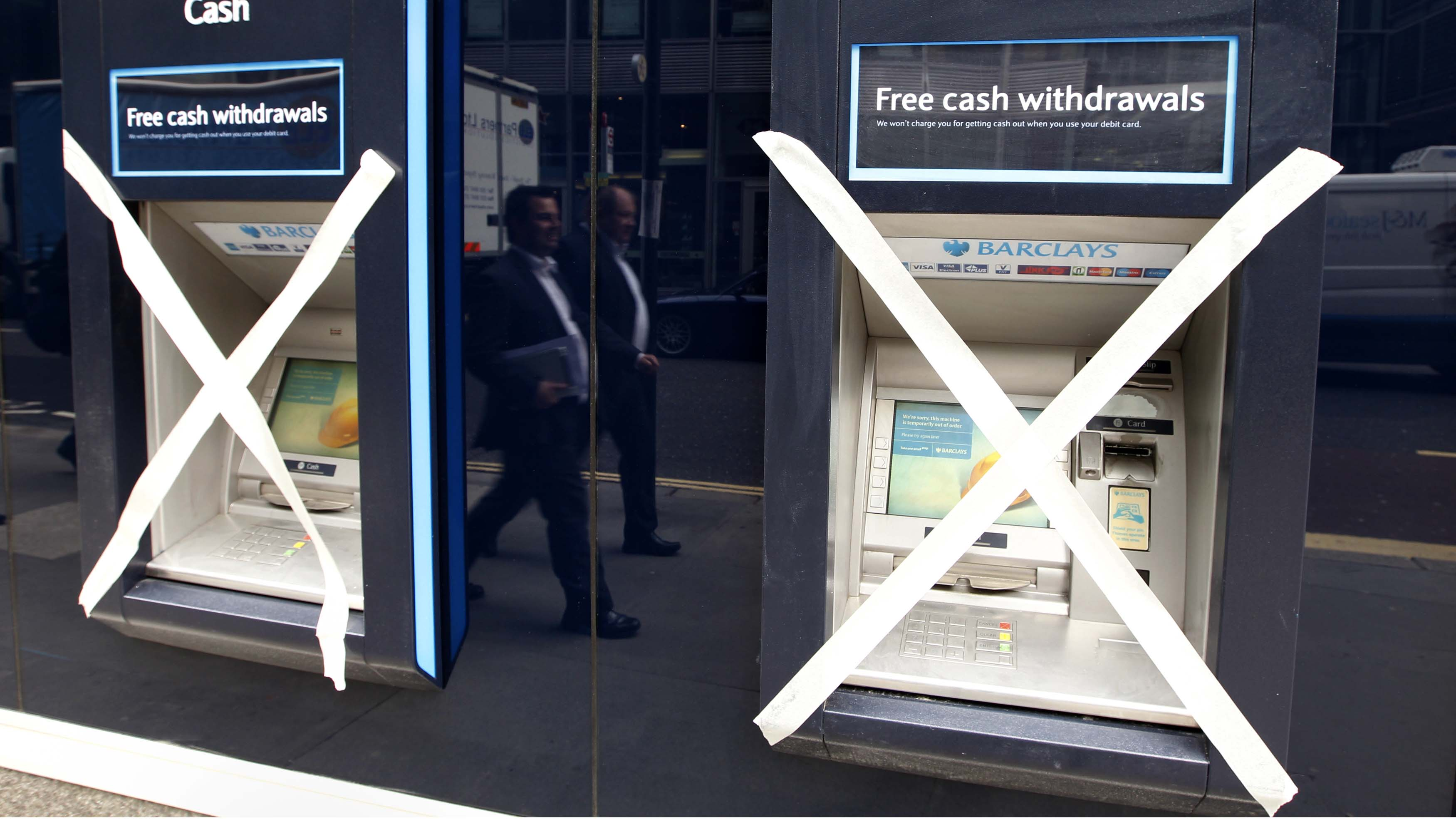 """Two men are reflected as they pass a pair of closed cashpoints marked with masking tape, outside a Barclays Bank branch being refurbished in the financial district City of London August 31, 2011. British Business Secretary Vince Cable accused the country's banks of trying to use the crisis in the eurozone to """"create a panic"""" and stave off industry reforms. Business and industry groups argue that a weak domestic economy and turmoil in the eurozone mean banks should not be burdened with extra regulation. REUTERS/Chris Helgren  (BRITAIN - Tags: POLITICS BUSINESS) - RTR2QKLX"""