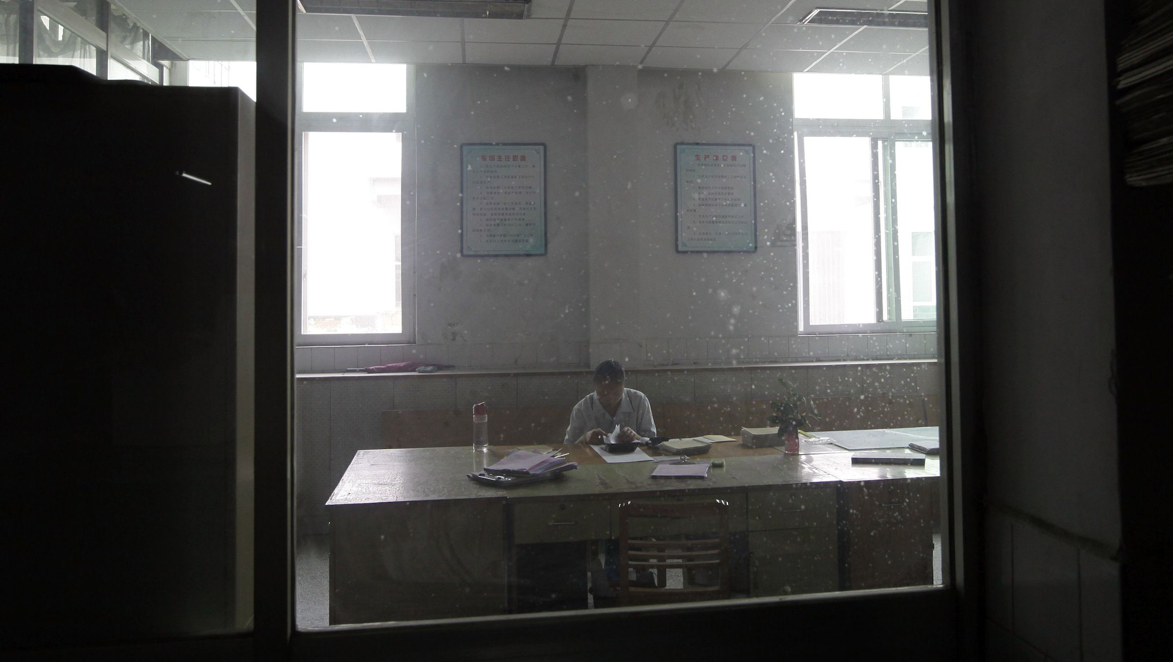 A woman works at an office of a printing factory of the Nanjie Cun Group in Nanjie village of Luohe city in China's central Henan province September 24, 2012. Nanjie village, with more than 3,100 residents, is touted to be one of the remaining models of communist China, where the principles of morality and collectivism of the late Chairman Mao still strictly guide the people's daily lives. Aside from free housing, healthcare, food rations and education, locals working in the village's factories receive an average salary of 2500 yuan, about 400 dollars. The village's return to communism came at the same time as the rest of the country opened up to the capitalist market in the mid 1980s. Mao is still highly revered in Nanjie, enjoying a god-like status.  Picture taken September 24, 2012.   REUTERS/Jason Lee (CHINA - Tags: POLITICS SOCIETY)  ATTENTION EDITORS: PICTURE 13 OF 33 FOR PACKAGE 'CHINA'S MODEL COMMUNISM' SEARCH 'NANJIE' FOR ALL IMAGES - RTR38H7N