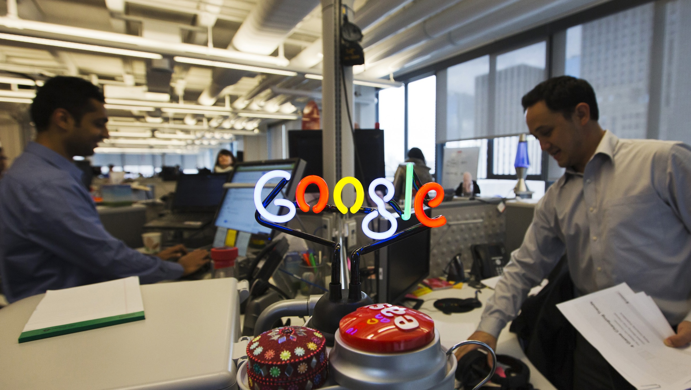 A neon Google logo is seen as employees work at the new Google office