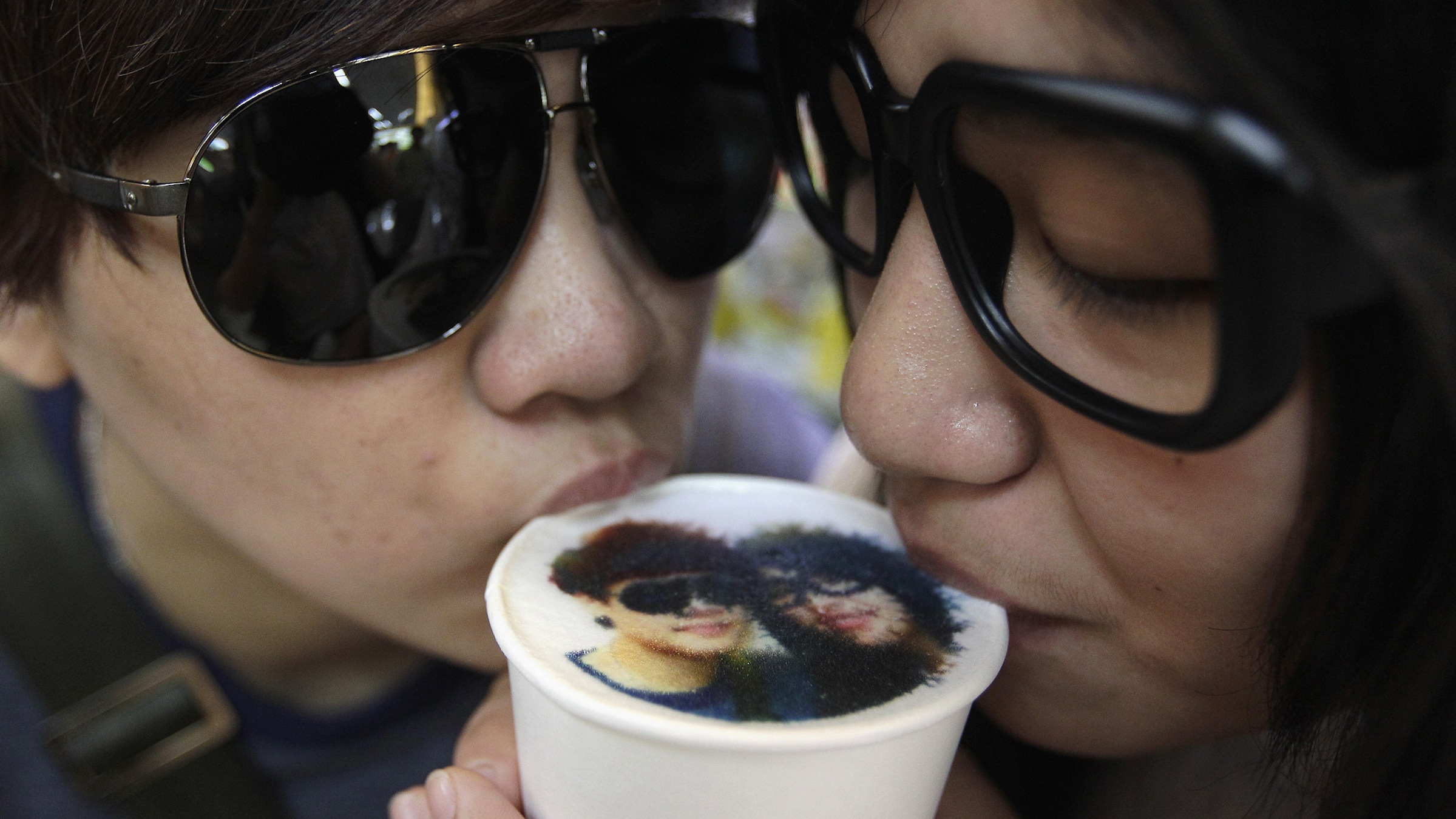 A couple drinks a cup of latte with their picture printed on top of the milk foam at a Family Mart in Taipei August 13, 2013. As part of Qixi Festival celebrations, customers of Family Mart's Let's Cafe were given the complimentary service of getting their pictures printed with edible inks on their lattes, according to a Family Mart employee. Qixi, also known as the Double Seventh Festival and the Chinese version of Valentine's Day, falls on the seventh day of the seventh month in the Chinese lunar calendar. REUTERS/Pichi Chuang (TAIWAN - Tags: ANNIVERSARY SOCIETY TPX IMAGES OF THE DAY) - RTX12JEZ