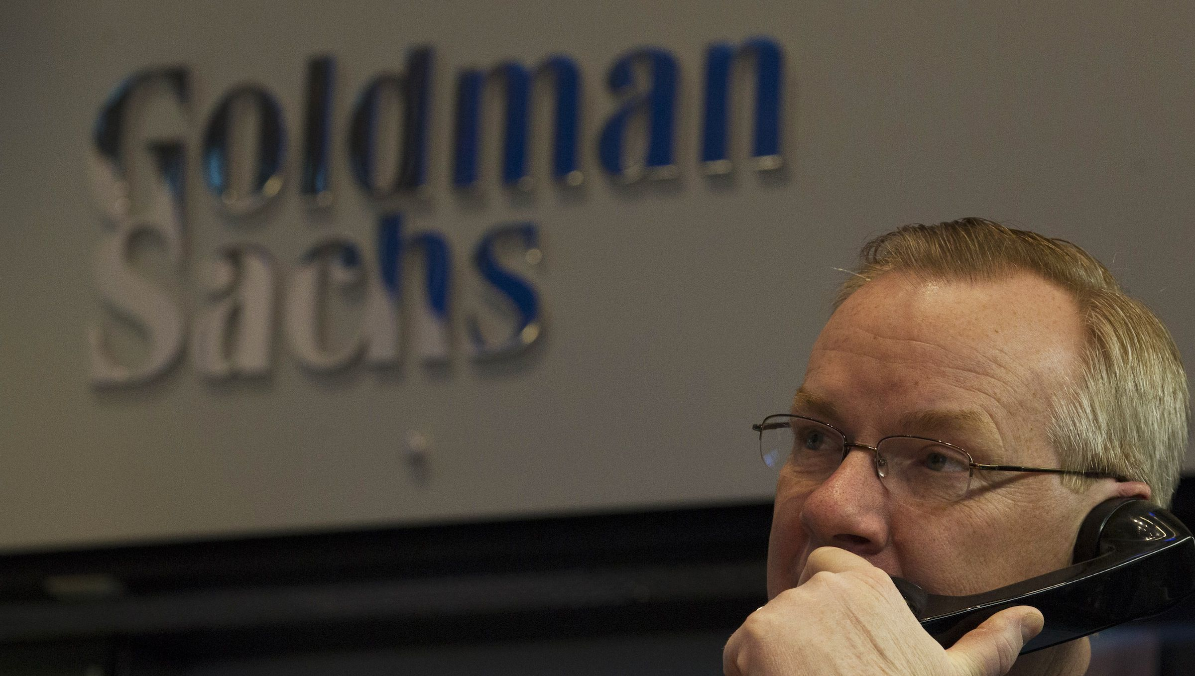 Goldman Sachs trader Dennis Maguire works in his company's stall on the floor of the New York Stock Exchange January 15, 2014.  REUTERS/Brendan McDermid (UNITED STATES - Tags: BUSINESS) - RTX17FM1