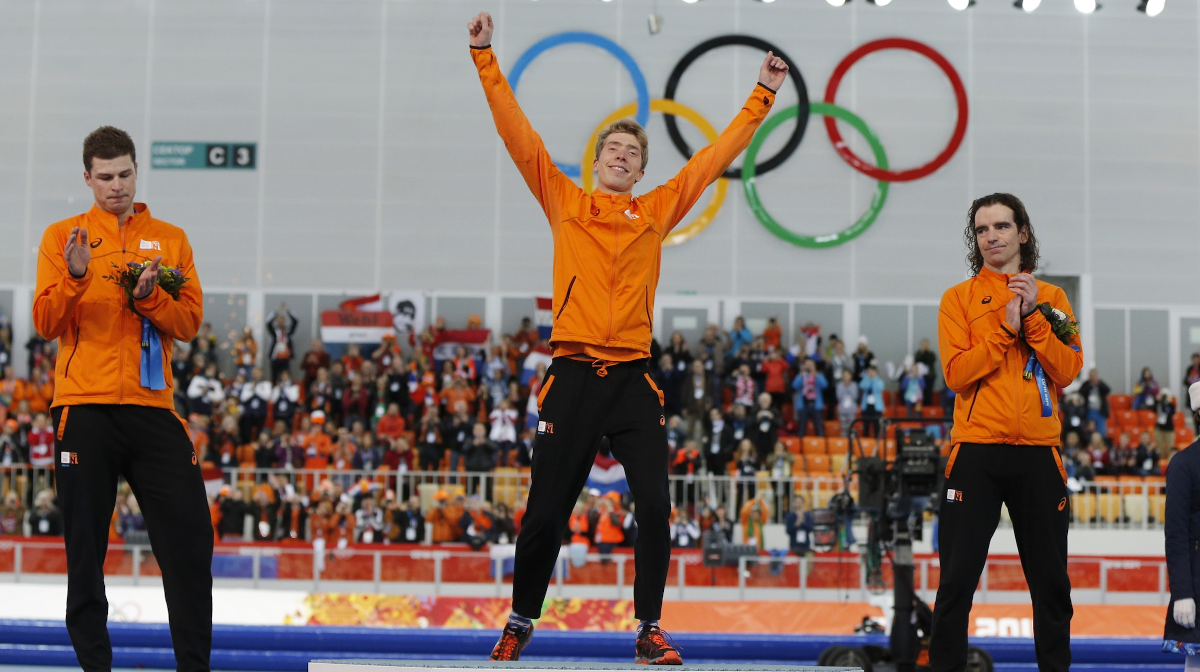 Second-placed Sven Kramer (L) of the Netherlands and his compatriot third-placed Bob de Jong (R) applaud winner Jorrit Bergsma of the Netherlands, during the flower ceremony for the men's 10,000 metres speed skating race at the Adler Arena in the Sochi 2014 Winter Olympic Games February 18, 2014. It was a fourth clean sweep of the speed skating medals for the Dutch at the Sochi Games.   REUTERS/Phil Noble (RUSSIA  - Tags: OLYMPICS SPORT SPEED SKATING TPX IMAGES OF THE DAY)   - RTX1920C