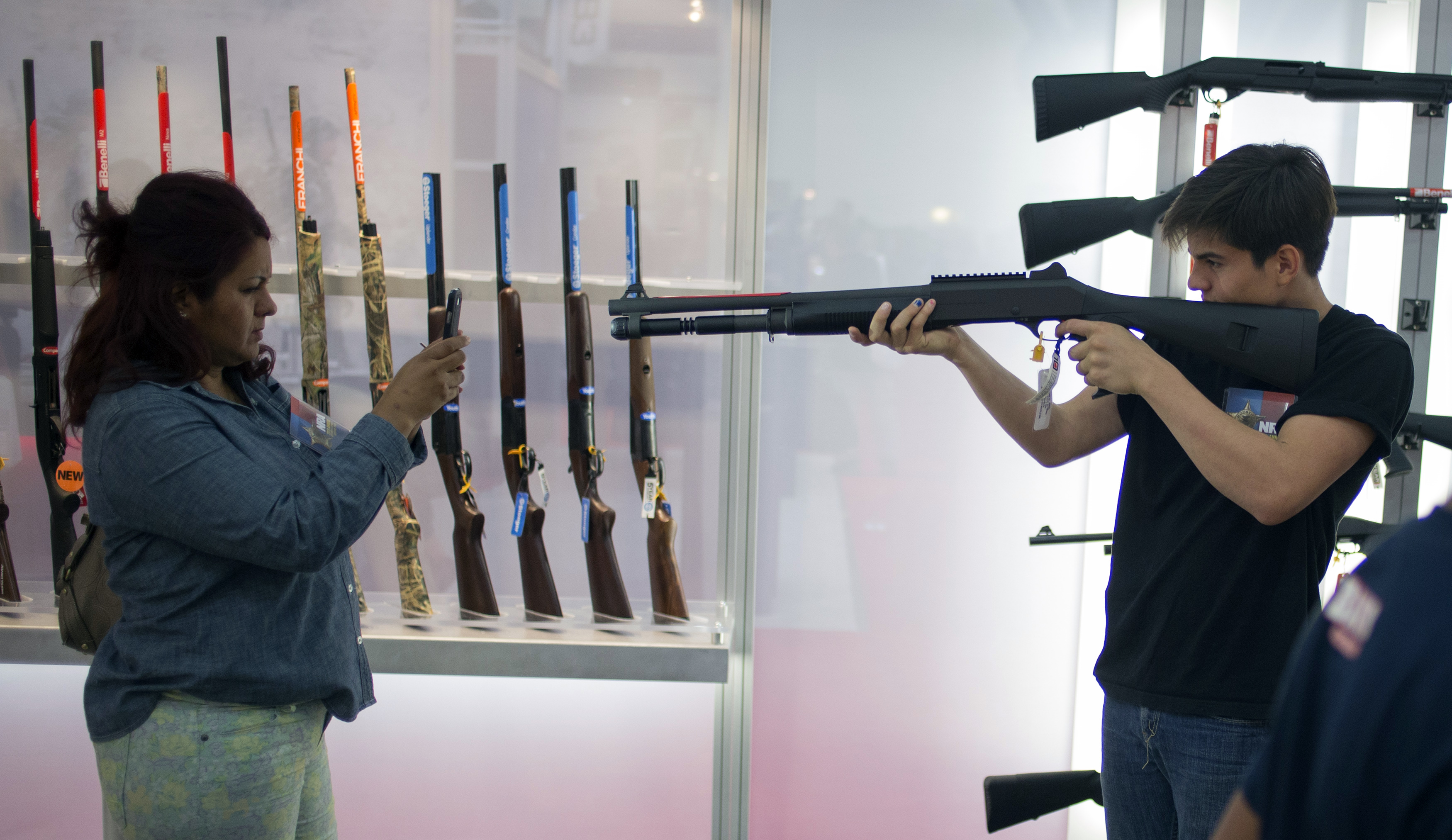 A woman uses a smart phone to photograph a young man holding a shotgun at an exhibit booth at the George R. Brown convention center, the site for the National Rifle Association's (NRA) annual meeting in Houston, Texas May 5, 2013.  REUTERS/Adrees Latif (UNITED STATES - Tags: POLITICS SOCIETY) - RTXZBWO