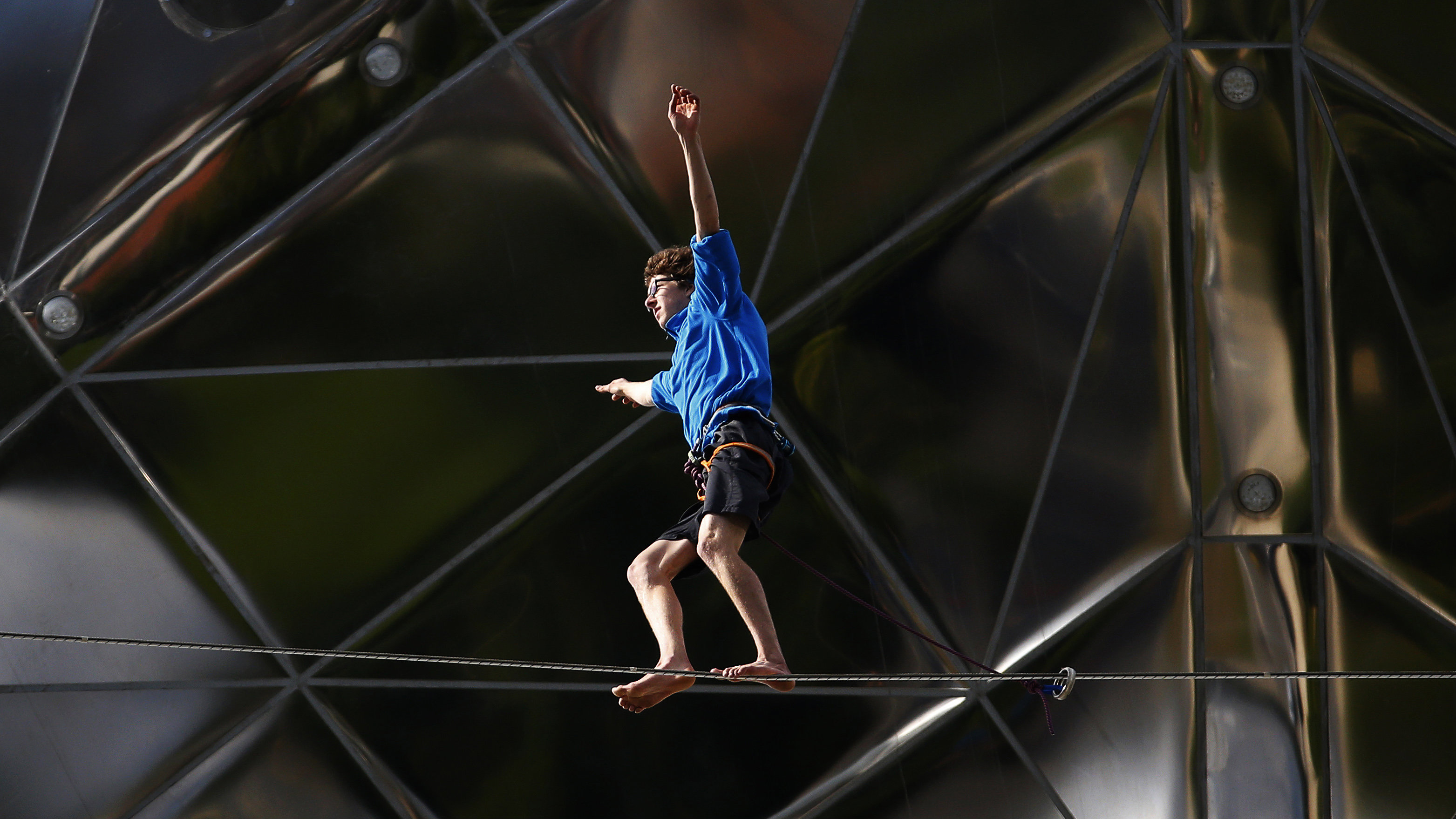 A tightrope walker performs between two spheres of the Atomium monument in Brussels August 11, 2014. The 102-metre-tall (335-feet-tall) structure and its nine spheres, which was designed for Expo 58, is in the shape of a unit cell of an iron crystal, magnified about 165 billion times.