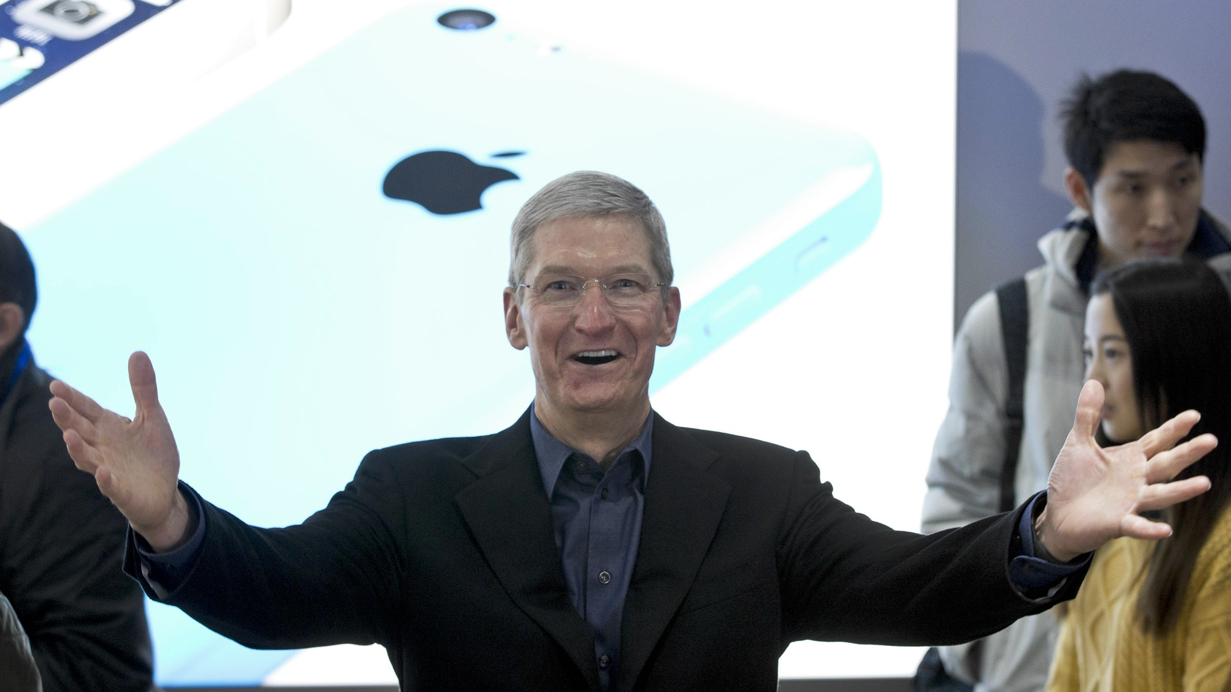 Apple's CEO Tim Cook gestures during a promotional event that marks the opening day of sales of China Mobile's 4G iPhone 5s and iPhone 5c at a shop of the world's largest mobile phone operator in Beijing, China, Friday, Jan. 17, 2014. (AP Photo/Alexander F. Yuan)