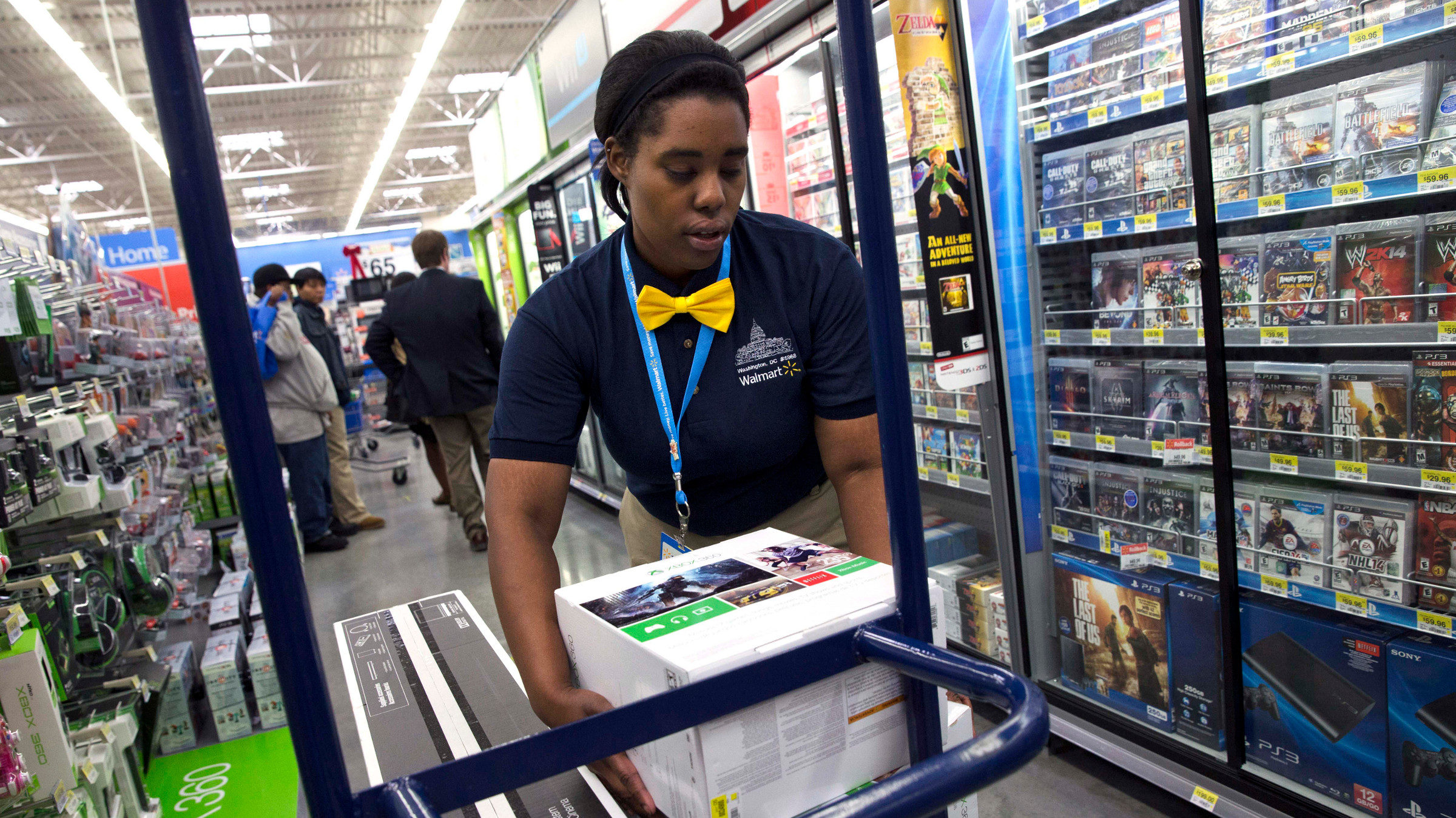 In this Wednesday, Dec. 4, 2013, photo, Tracey Anderson, 26, re-stocks X-Box sets on opening day of a new Wal-Mart on Georgia Avenue Northwest in Washington. Wal-Mart said Friday, Jan. 31, 2014, that its fiscal fourth-quarter and full-year adjusted earnings from continuing operations may come in at or slightly below the low end of its prior forecasts.