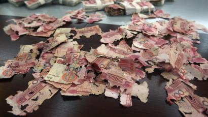 Damaged 100 yuan banknotes are seen on a table at a branch of China Bank in Foshan, Guangdong province, June 5, 2013. A woman brought about 400,000 yuan ($65,200), which she had kept at home, to the bank for replacement after most of the notes were bitten by white ants. Her notes were exchanged for new ones but for 60,000 yuan ($9,780) which the bank assessed and declared to be unchangeable. Picture taken June 5, 2013. REUTERS/Stringer