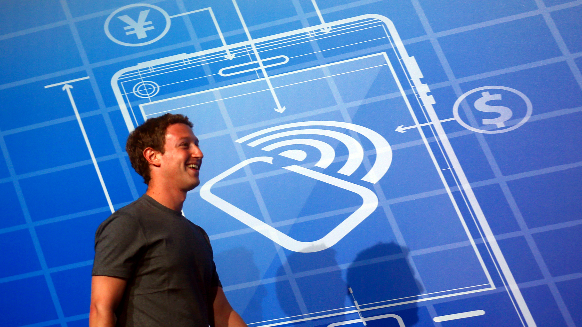Facebook Chief Executive Officer Mark Zuckerberg smiles as he arrives at the stage to deliver a keynote speech during the Mobile World Congress in Barcelona February 24, 2014. Zuckerberg will take a victory lap at the world's largest mobile technology conference in Barcelona on Monday, after beating out Google Inc in a $19 billion acquisition of free messaging service WhatsApp.