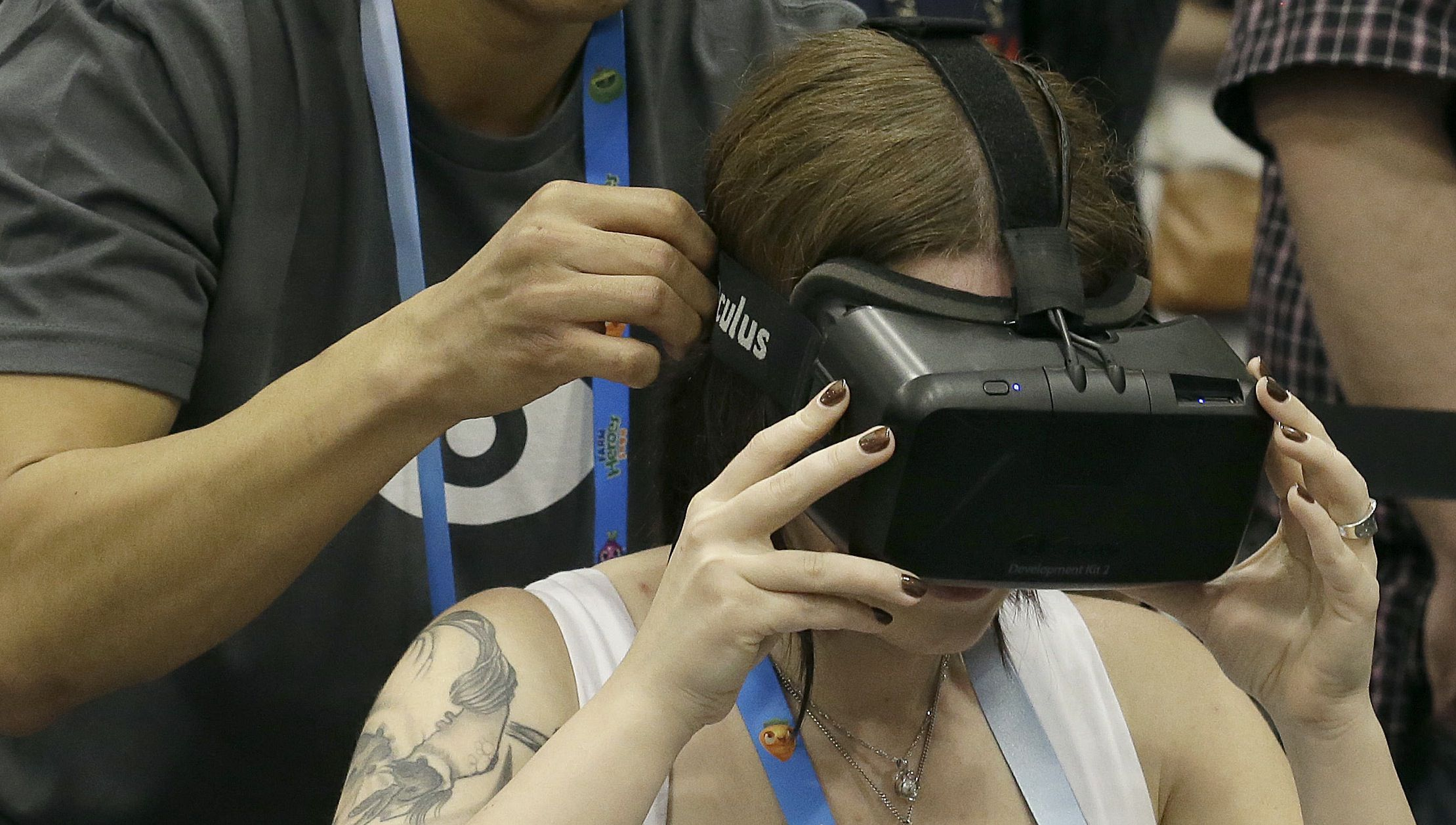 David Ninh helps put an Oculus virtual reality headset onto Lana Ansay at the Game Developers Conference 2014 in San Francisco, Wednesday, March 19, 2014. (AP Photo/Jeff Chiu)