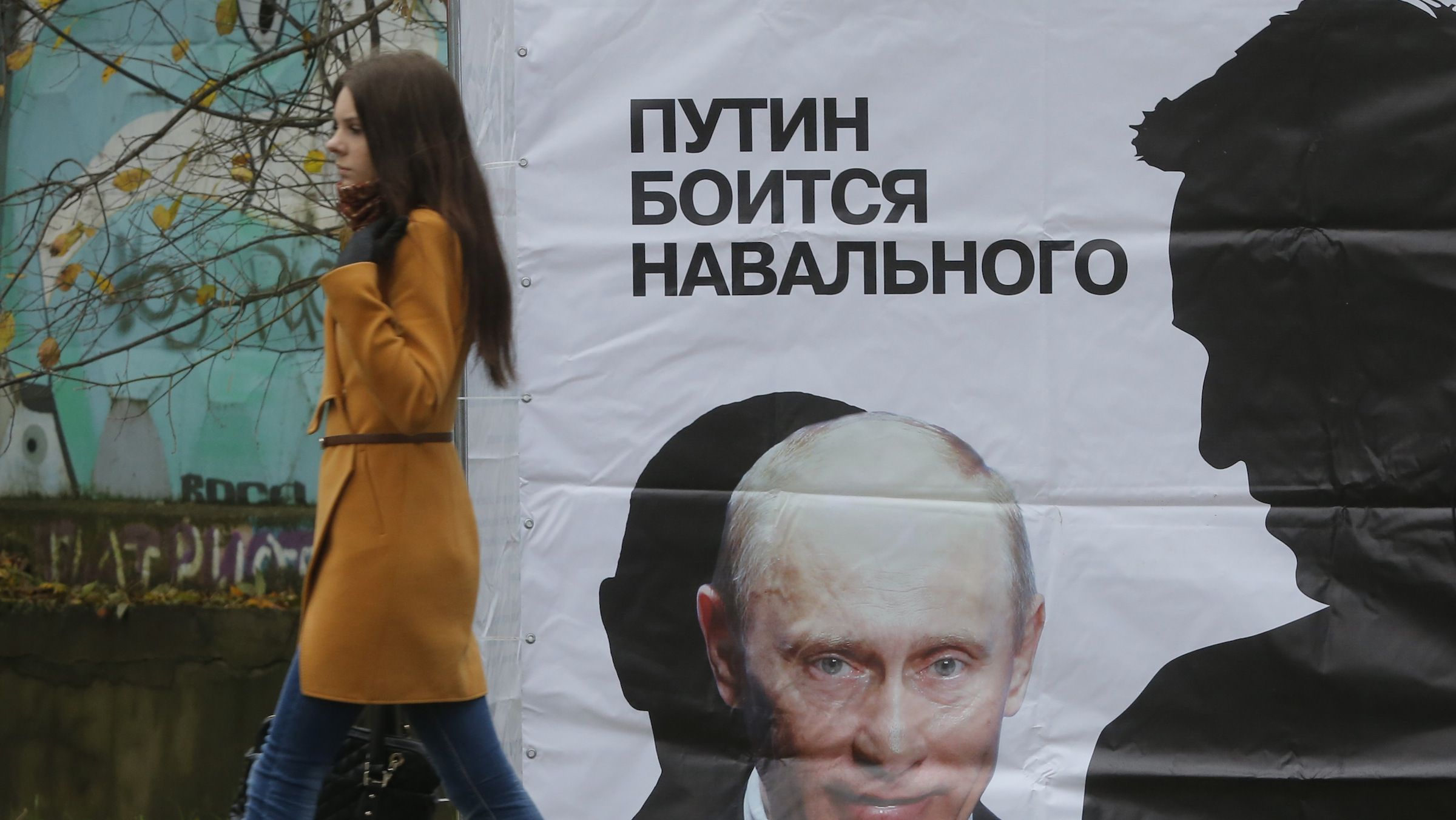 """A woman passes a poster reading """"Putin is afraid of Navalny"""" in a street in Kirov, Russia, Wednesday, Oct. 16, 2013. The judge of a Russian court has overturned a sentence for opposition leader and anti-corruption blogger Alexei Navalny, handing him a suspended sentence instead of five years in prison. (AP Photo/Dmitry Lovetsky)"""