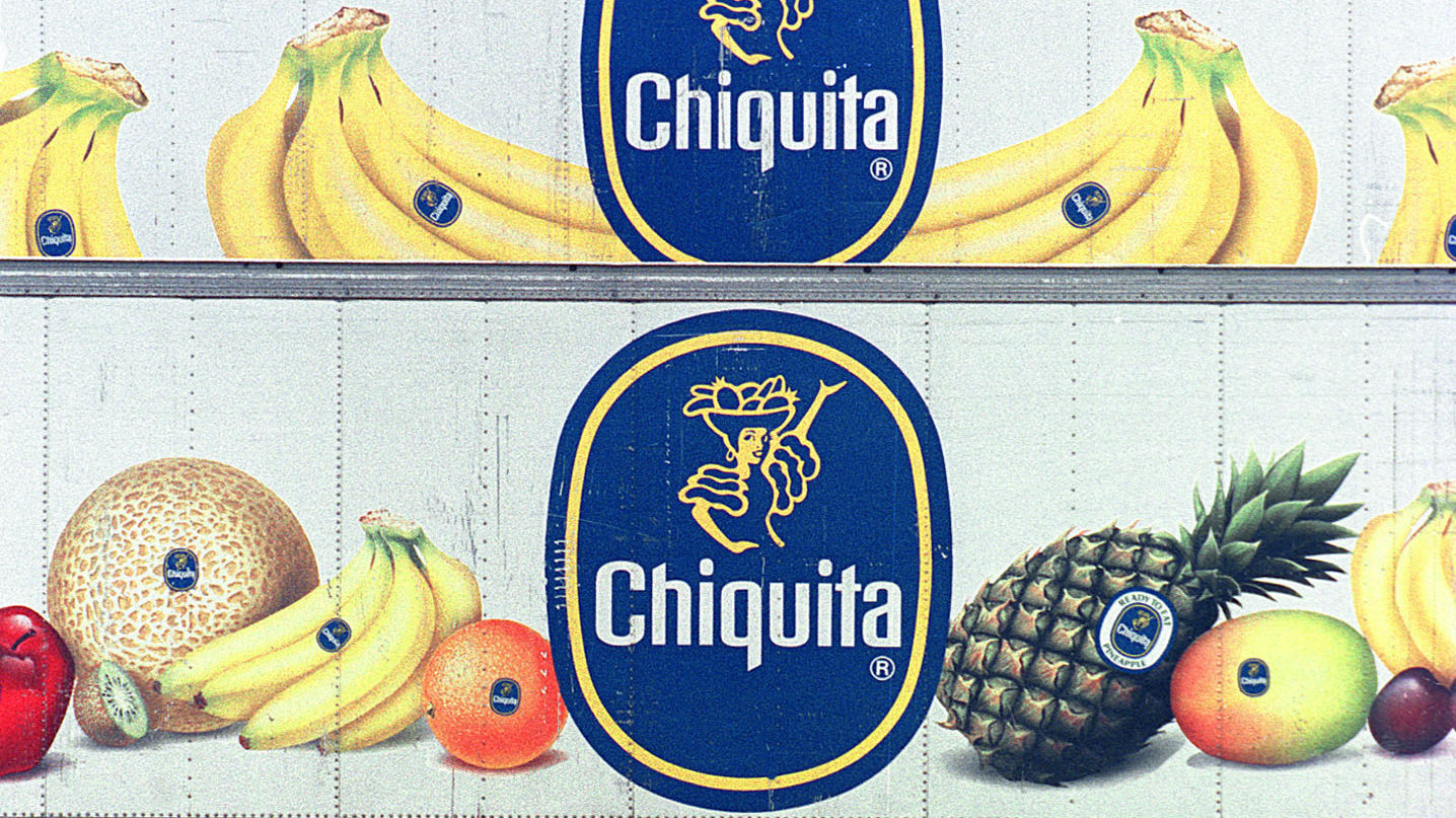 A dock worker at Almirante port on Panama's Atlantic coast walks past containers with the logo of multinational fruit company Chiquita, October 10, 2002. The containers will be shipped full of bananas to Europe. After 100 years in Panama, Chiquita is considering closing its operations because of mounting losses, especially at its Pacific plantations.