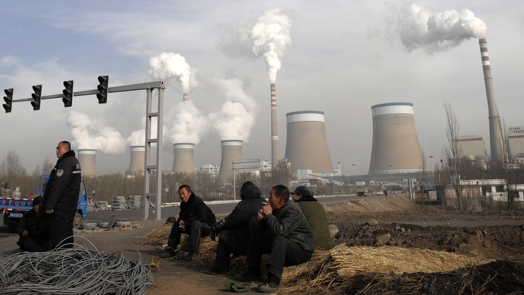 In this Dec. 3, 2009 file photo, Chinese workers take a break in front of the cooling towers of a coal-fired power plant in Dadong, Shanxi province, China. China told the United States on Wednesday, March 10, 2010, to make stronger commitments on climate change and provide environmental expertise and financing to developing nations. (AP Photo/Andy Wong