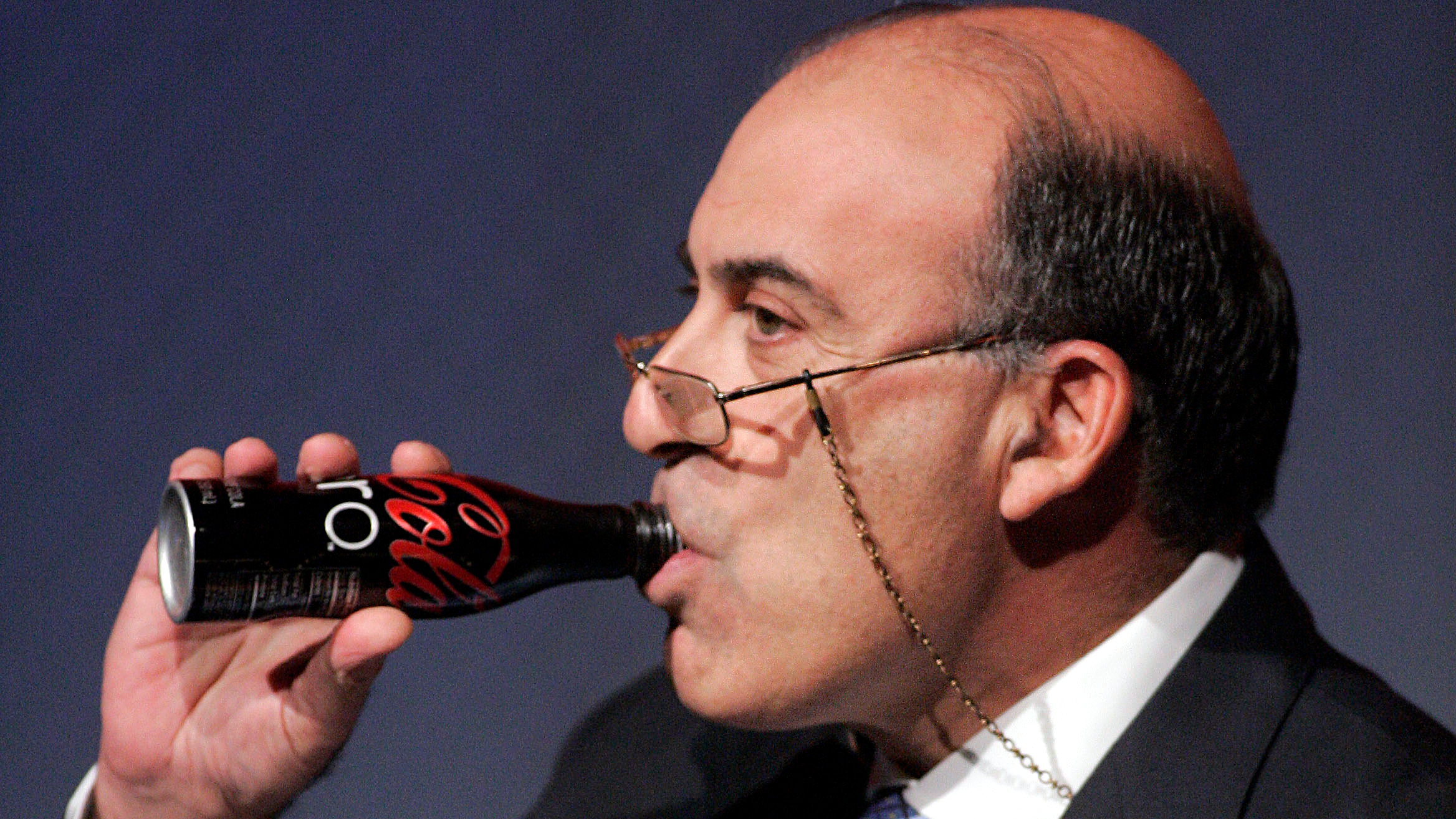 Coca-Cola CEO Muhtar Kent takes a drink of a Coca-Cola Zero while addressing investors at a conference in which a vision for the future of the company is announced, Monday Nov. 16, 2009, in Atlanta.