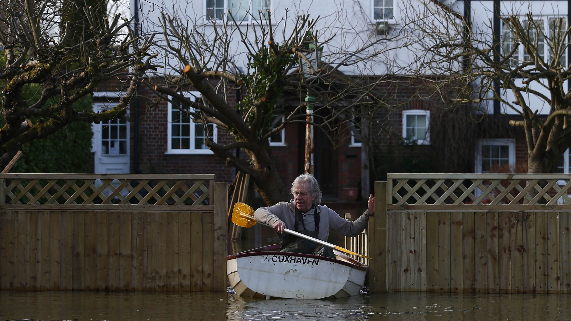 Nigel Gray leaves his home in a rowing boat after the river Thames flooded the village of Wraysbury, southern England February 10, 2014. REUTERS/Eddie Keogh