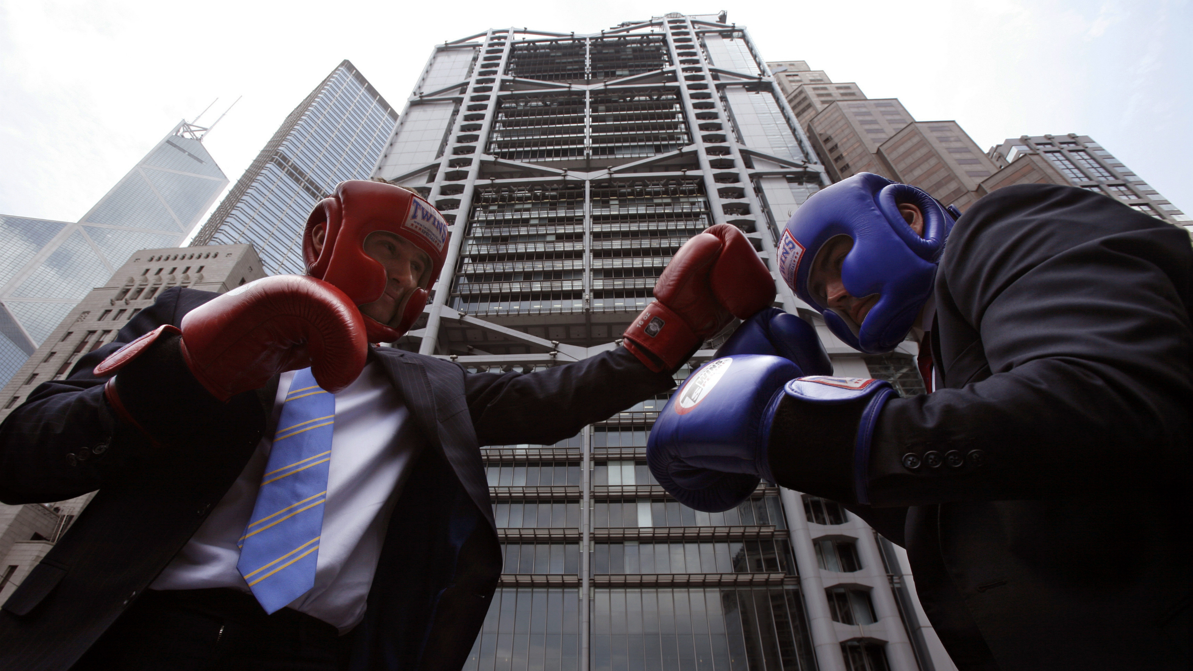 """Neil Hutchinson (L), Senior Wealth Manager of HSBC, poses with James Bryan in hedge fund management from Execuzen, outside HSBC headquarters during a promotion ahead of a """"Hedge Fund Fight Nite"""" charity event in Hong Kong September 2, 2009. Twelve of the 44 financiers who initially signed up to participate in the event will fight in the final rounds in October while 800 of their peers from the corporate and finance world of Hong Kong watch, according to a press release. REUTERS/Bobby Yip"""
