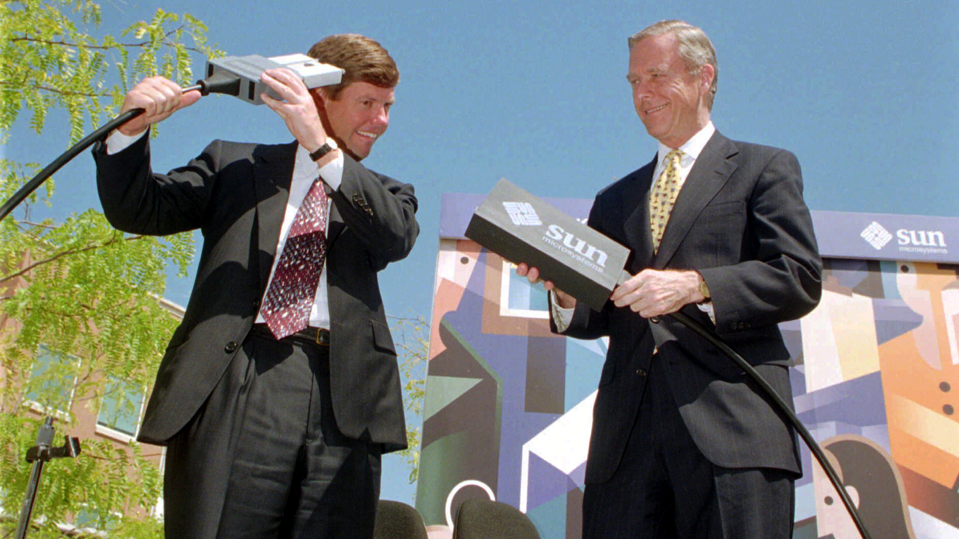 Sun Microsystems Inc. CEO Scott McNealy, left, jokes around with a fiber optic cable connection, during a news conference with Calif. Gov. Pete Wilson, right, at Sun Microsystem's Menlo Park, Calif. facility, Wednesday, Aug. 24, 1994. It has been reported that Sun Microsystems Inc. is preparing a bid for the financially struggling Apple Computers Inc. Sun's main focus is workstations and internet servers and an acquisition of Apple would give Sun access to the fast-growing market for desktop computers.
