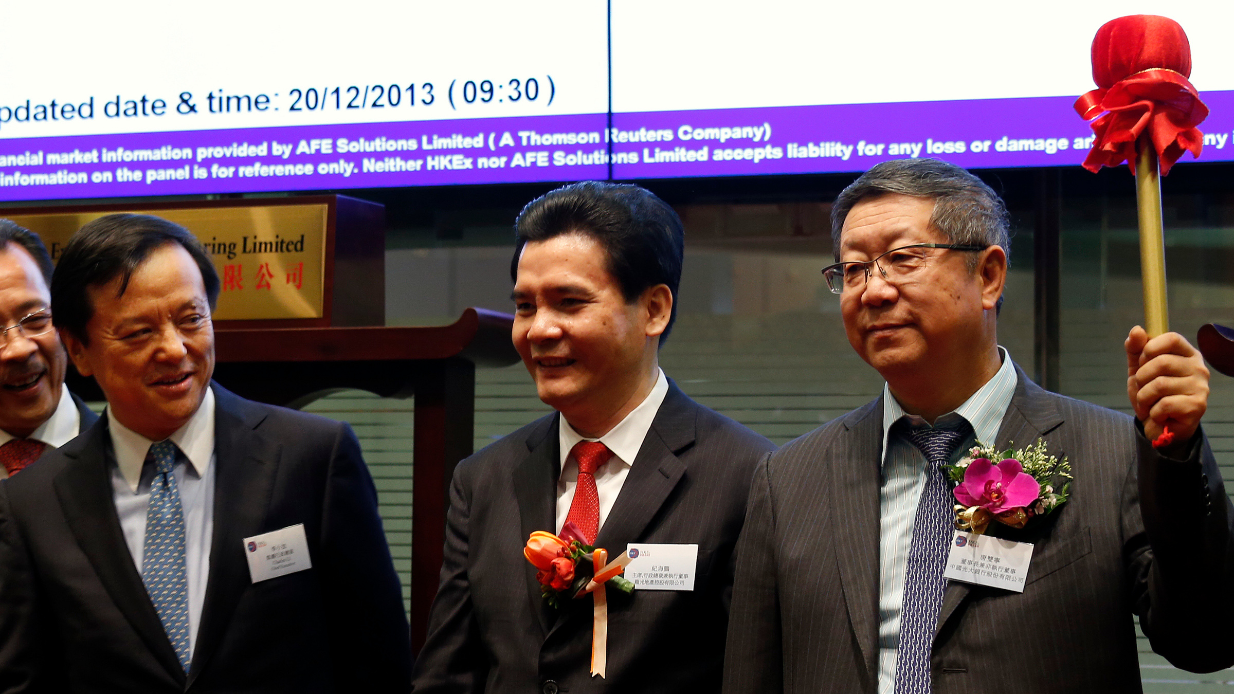 China Everbright Bank's Chairman Tang Shuangning (R) gestures after hitting a gong as Hong Kong Exchange Chief Executive Charles Li (L) looks on during the debut of the bank at the Hong Kong Stock Exchange December 20, 2013. China Everbright Bank Co Ltd is set to fall 0.8 percent in its Hong Kong trading debut on Friday, after the mid-sized lender raised $3 billion in a share offering priced near the bottom of expectations. Standing between them is Logan Property Holdings' Chairman Ji Haipeng, whose company also debut on Friday.