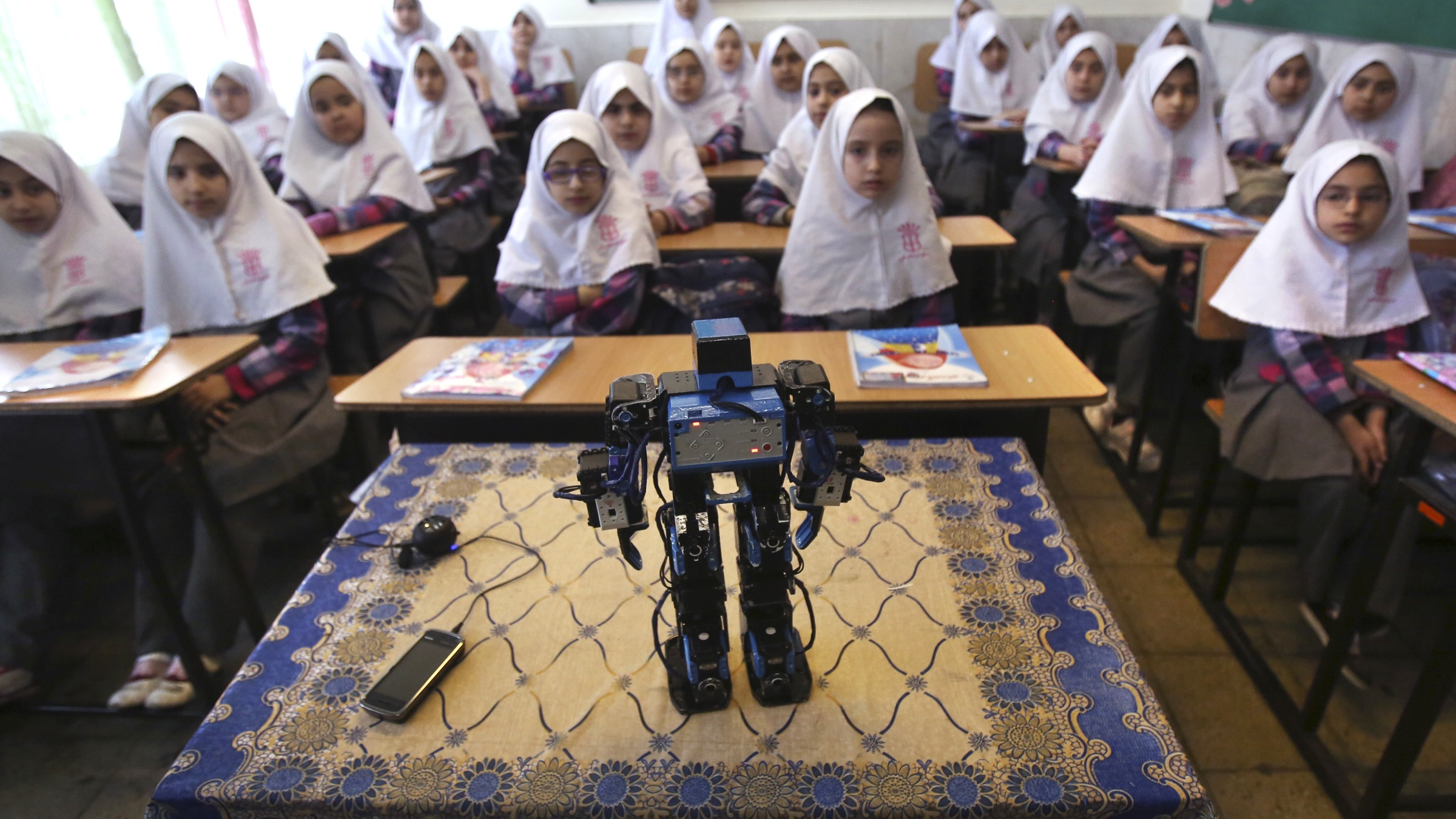 "In this picture taken on Monday, Feb. 24, 2014, Veldan, a humanoid praying robot which is built by Iranian schoolteacher Akbar Rezaie, performs morning prayer in front of Alborz elementary school girls in the city of Varamin some 21 miles (35 kilometers) south of the capital Tehran, Iran. Rezaei who has built a robot to show to children how to execute daily prayers, has innovated an amusing way of encouraging young children to say their daily prayers by using the science of robotics. Out of personal interest and unrelated to his field of study, Akbar Rezaei attended private robotics classes and acquired the skill of assembling and developing customized humanoid robots. He built the robot at home with basic tools and gave it the designation ""Veldan"", a term mentioned in Quran meaning: ""Youth of Heaven"".  By applying some mechanical modifications such as adding up two extra engines Akbar Rezaei managed to let the robot perform praying movements, such as prostration, more easily.(AP Photo/Vahid Salemi)"