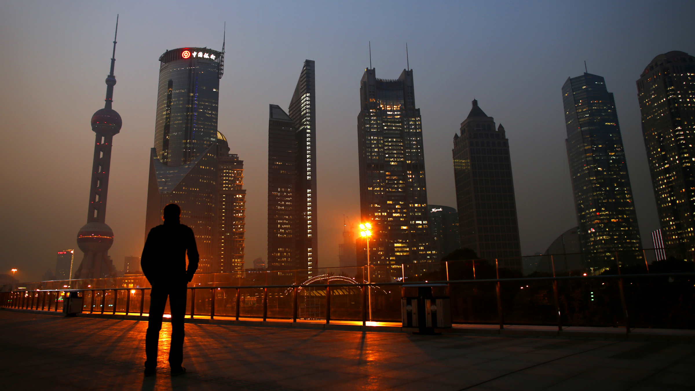 A man looks at the Pudong financial district of Shanghai November 20, 2013. With a shift in tone and language, China's central bank governor has dangled the prospect of speeding up currency reform and giving markets more room to set the yuan's exchange rate as he underlines broader plans for sweeping economic change. The central bank under Zhou Xiaochuan has consistently flagged its intention to liberalise financial markets and allow the yuan to trade more freely, even before the Communist Party's top brass unveiled late last week the boldest set of economic and social reforms in nearly three decades. REUTERS/Carlos Barria