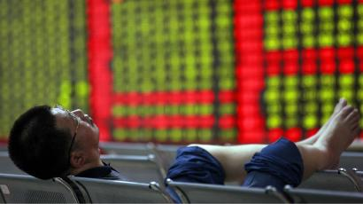 An investor sleeps on a bench in front of an electronic board showing stock information at a brokerage house in Huaibei, Anhui province May 9, 2012. China shares produced its worst loss in six weeks on Wednesday, hit by weakness in growth-sensitive sectors on jitters that a possible delay to the start of the country's five-yearly congress could complicate economic recovery. The green figures on screen indicate falling prices. REUTERS/Stringer
