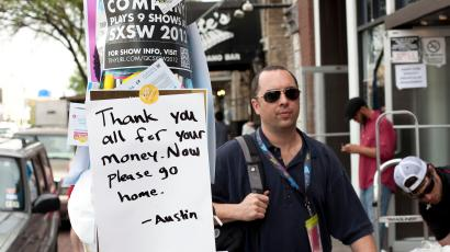 A man walks next to a sign posted on the street during the South by Southwest (SXSW) Music conference in Austin, Texas March 13, 2012. REUTERS/Julia Robinson (UNITED STATES - Tags: ENTERTAINMENT) - RTR2ZB2V