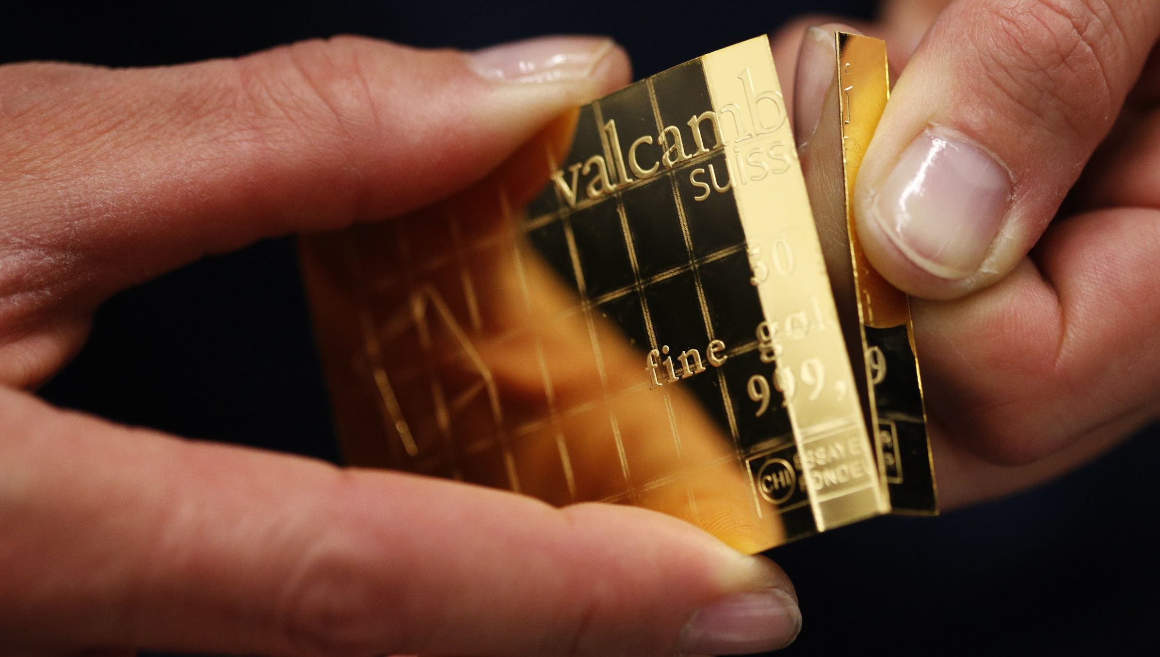 An employee shows dividing a gold Combibar at a plant of gold refiner and bar manufacturer Valcambi SA in the southern Swiss town of Balerna December 20, 2012. The divisible gold combibar has a purity of 99.9 percent, weighs 50 grams and also has predetermined breaking points which allow it to be easily separated without any loss of material into 1 gram pieces. Picture taken December 20, 2012. To match story SWISS-GOLD/ REUTERS/Michael Buholzer (SWITZERLAND - Tags: BUSINESS) - RTR3BT5P