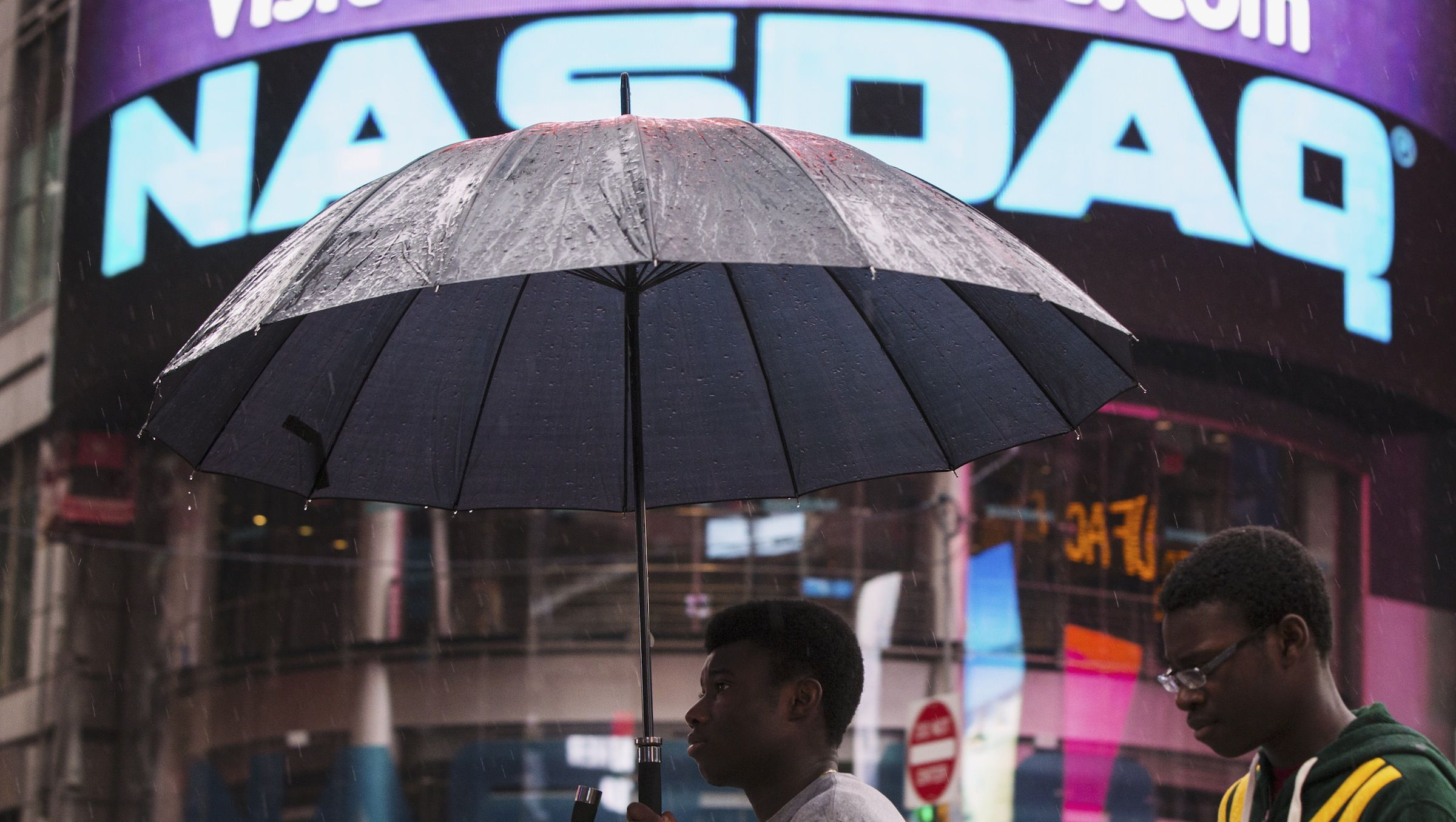A man holds up an umbrella as he walks past the Nasdaq MarketSite in New York's Times Square, August 22, 2013. Trading in a large part of the U.S. market came to a halt for much of Thursday after an unexplained issue shut down trading on Nasdaq-listed securities, the latest black eye for the U.S. securities trading business.   REUTERS/Lucas Jackson (UNITED STATES - Tags: BUSINESS ENVIRONMENT) - RTX12TKG