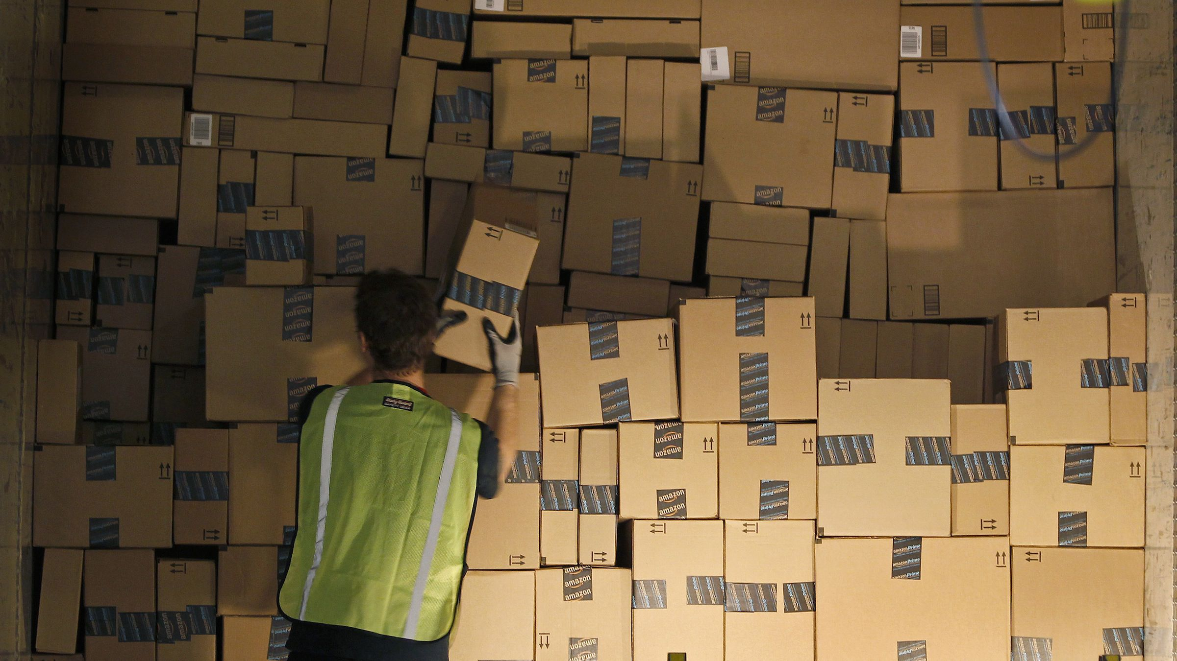 A worker stacks a shipping trailer with boxed items for delivery at Amazon's distribution center in Phoenix, Arizona November 22, 2013. The web-based retailer is preparing for Cyber Monday, traditionally the busiest day of the year for online purchases, which falls on December 2 in 2013. REUTERS/Ralph D. Freso   (UNITED STATES - Tags: BUSINESS EMPLOYMENT) - RTX15PA1