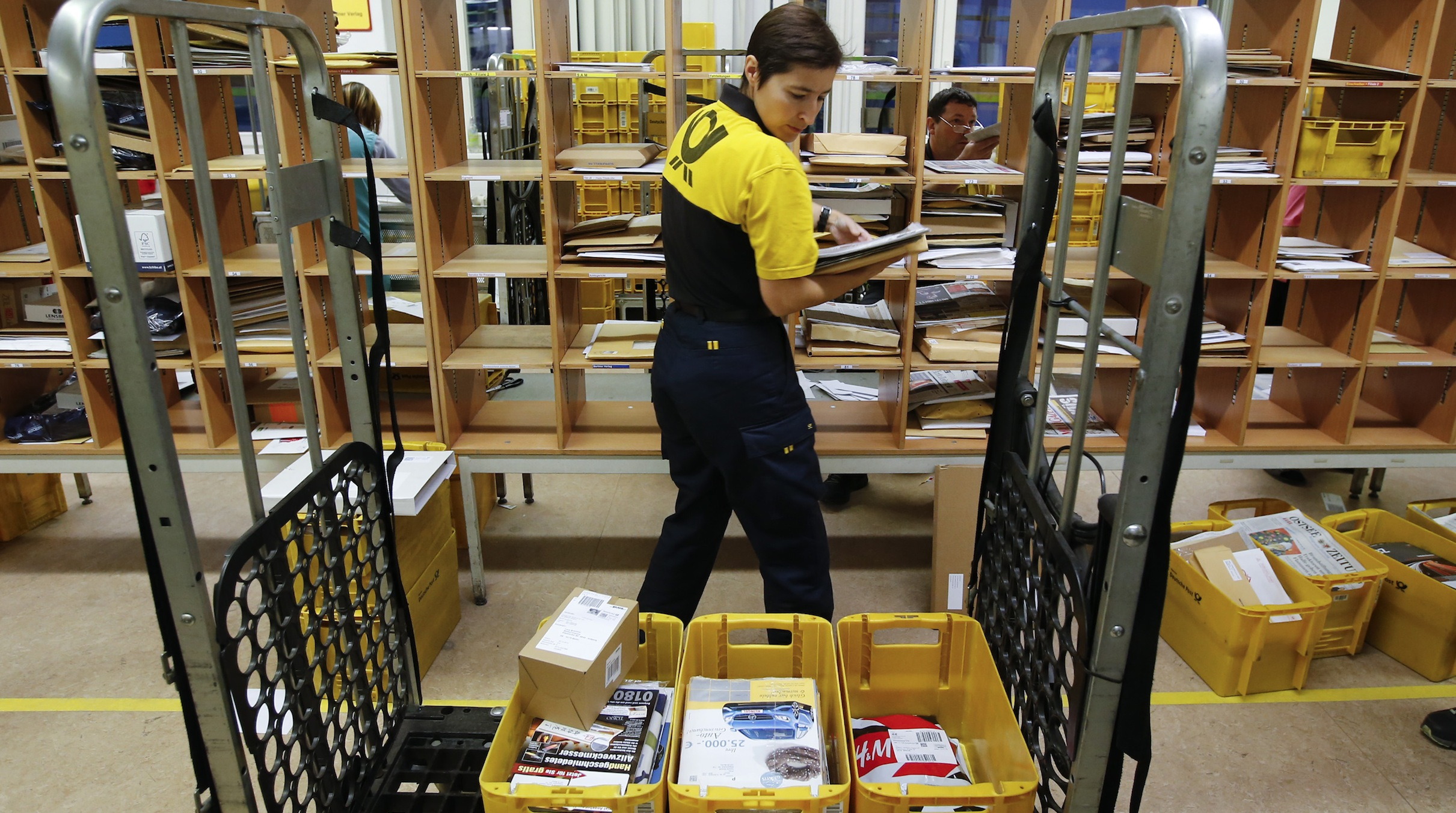 A postwoman of the German postal and logistics group Deutsche Post sorts mail at a sorting office in Berlin's Mitte district, December 4, 2013. Deutsche Post, the world's number one postal and logistics group, transported around 18 billion letters in 2012. REUTERS/Fabrizio Bensch (GERMANY  - Tags: BUSINESS EMPLOYMENT) - RTX16409