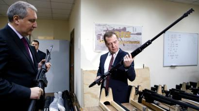 Russian Prime Minister Dmitry Medvedev (R) holds a weapon while listening to an explanation given by his deputy Dmitry Rogozin, during an inspection of Russian-made firearms at Promtechnologiya company in Moscow November 19, 2013.