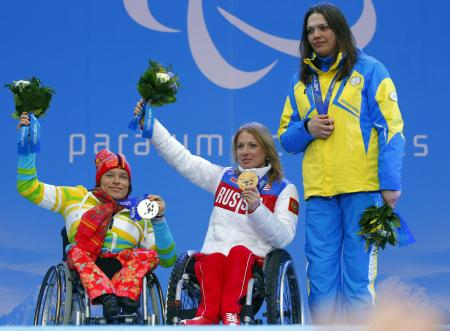 Ukraine's Olena Iurkovska covers her bronze medal with her hand after finishing third in the women's biathlon 12,5 km sitting event as she and first place Svetlana Konovalova of Russia, center and second place Anja Wicker of Germany pose during a medal ceremony at the 2014 Winter Paralympics, Friday, March 14, 2014, in Krasnaya Polyana, Russia. The majority of Ukraine's Paralympic medalists covered their medals during medal ceremonies. (AP Photo/Dmitry Lovetsky)