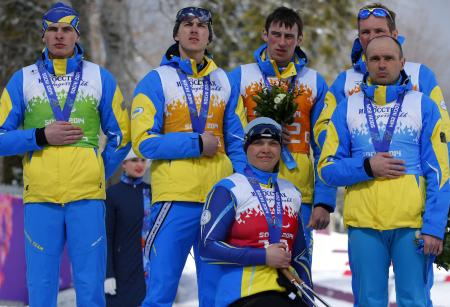 Ukraine's team, from left: Ihor Reptyukh, Vitaliy Kazakov, Olena Iurkovska, Iurii Utkin, Borys Babar and Vitaliy Lukyanenko cover their silver medals with their hands after finishing second in cross country 4x2.5km open relay at the 2014 Winter Paralympic, Saturday, March 15, 2014, in Krasnaya Polyana, Russia. The majority of Ukraine's Paralympic medalists covered their medals during medal ceremonies. (AP Photo/Dmitry Lovetsky)